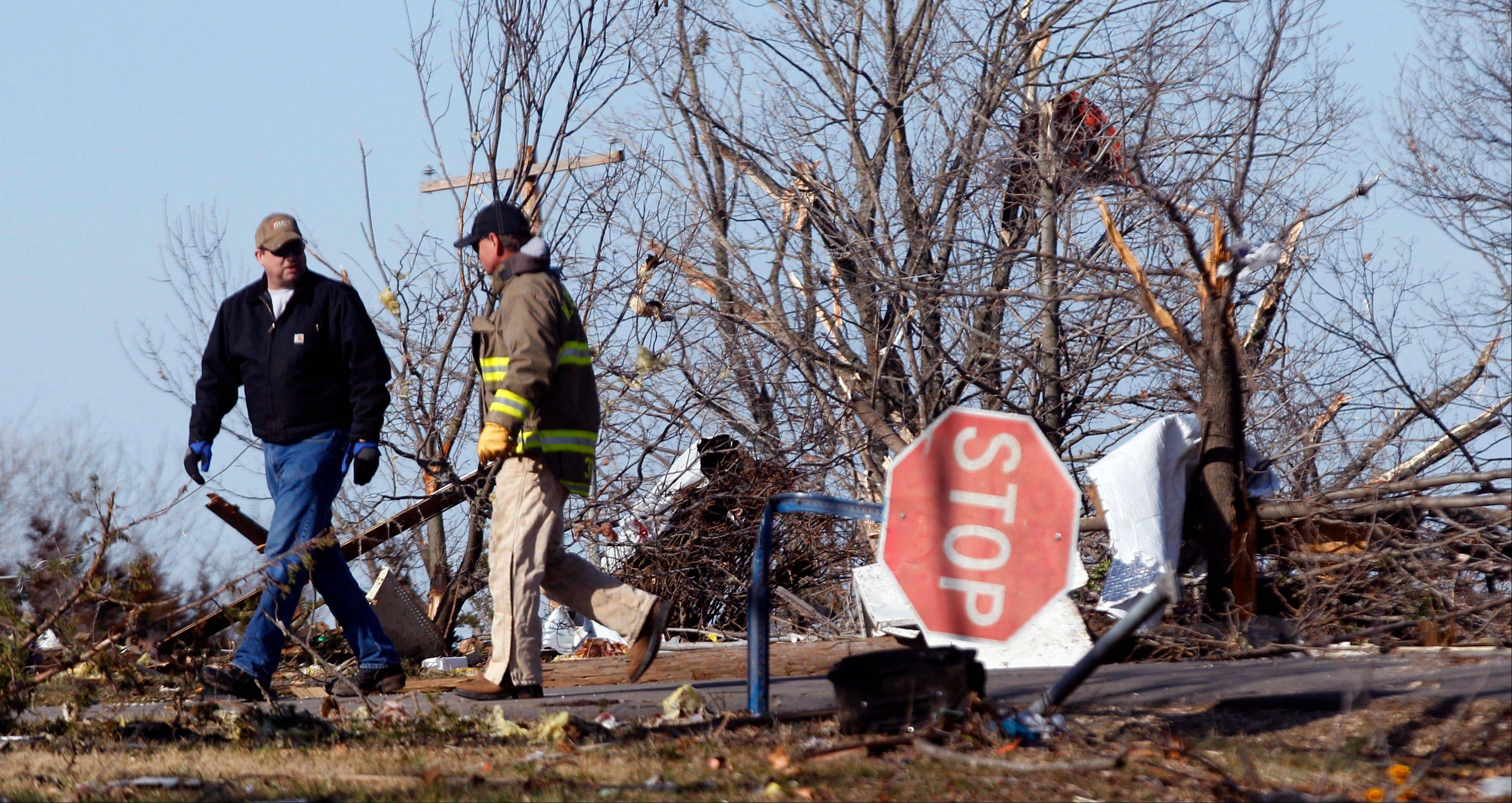 Volunteers walk past storm damage in Harveyville, Kan., Wednesday, Feb. 29, 2012. A powerful storm system lashed the Midwest early Wednesday, roughing up the country music resort city of Branson and laying waste to the small town in Kansas.