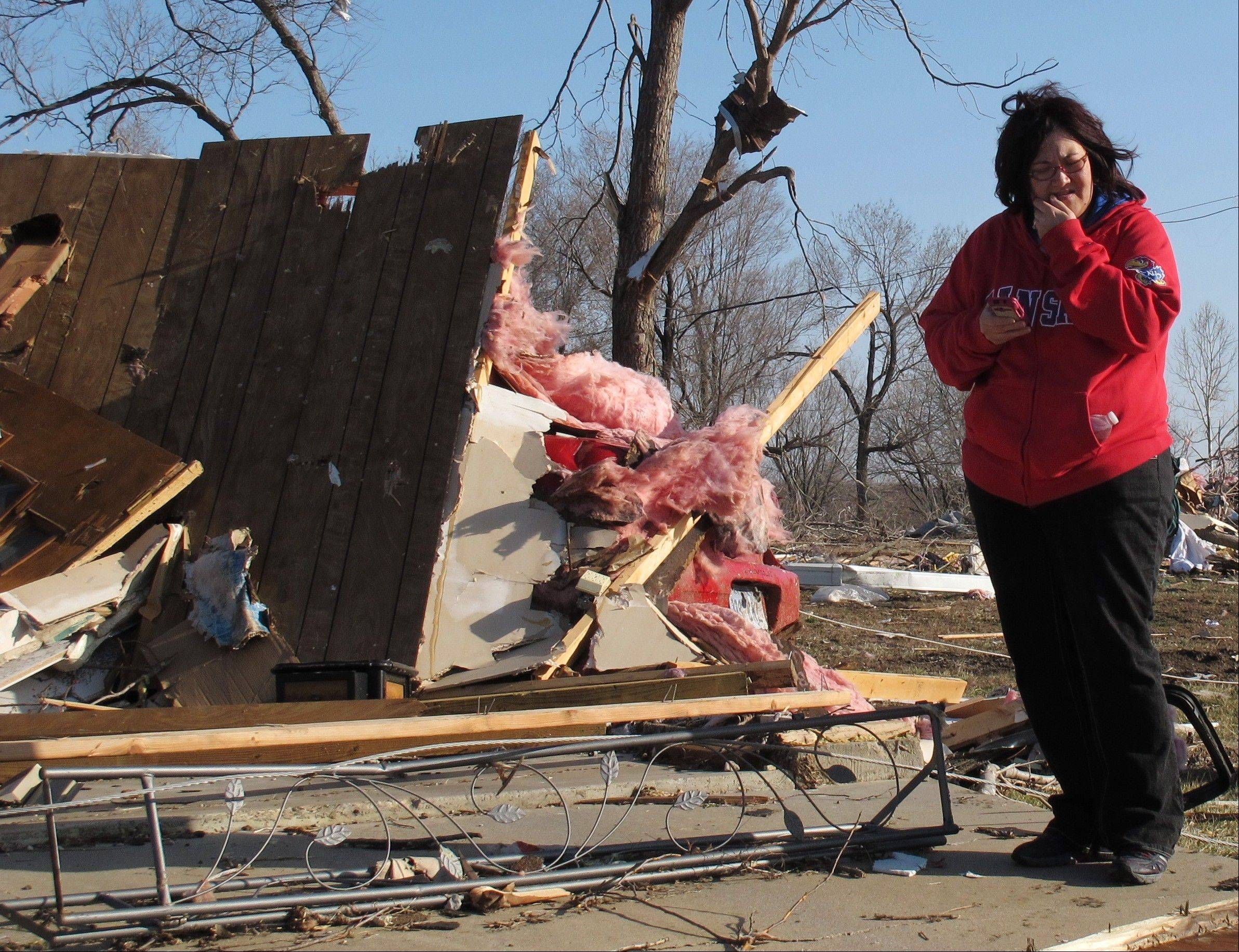 Tammy Woodyard, of Harveyville, surveys the wreckage of her father's home the morning after a tornado hit the town, Wednesday, Feb. 29, 2012, in Harveyville, Kan. Her father was unhurt.