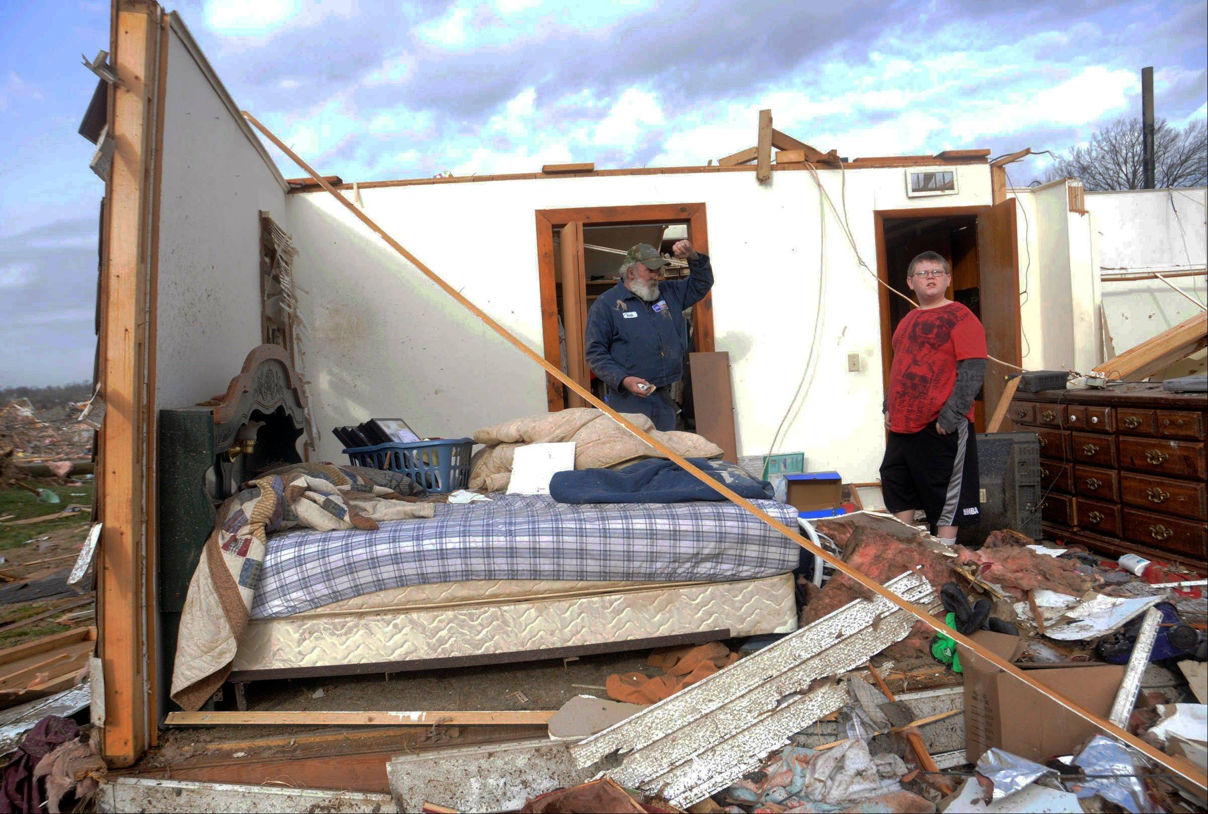 Keith Hucke, left, and Devyn Byrd, 14, survey the damage sustained to Hucke's house after a severe storm hit in the early morning hours on Wednesday, Feb. 29, 2012, in Harrisrbug, Ill. Hucke said he was in his bed when the wall right next to him collapsed during the storm. A severe pre-dawn storm pounded portions of southern Illinois on Wednesday. Several deaths have been reported in Harrisburg and left the city's medical center scrambling to treat an influx of injured, the hospital's top administrator said.