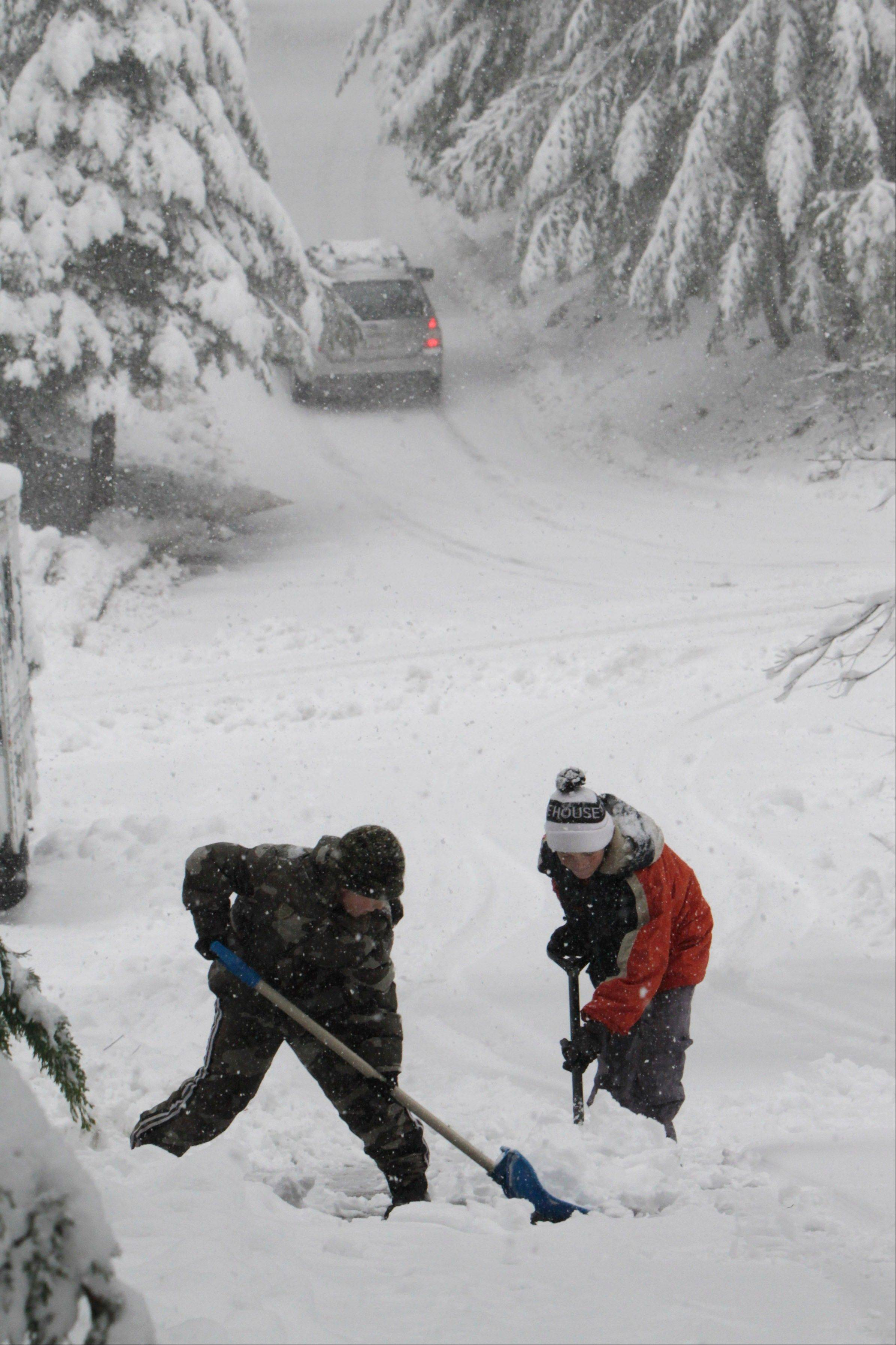 Ethan Mulhollen, 8, left, and James Roberts, Jr., 13, dig out a driveway in Pollock Pines, Calif., Wednesday, Feb. 29, 2012. The Sierra Nevada received between 6-12 inches of snow overnight in a series of storms that are long overdue.