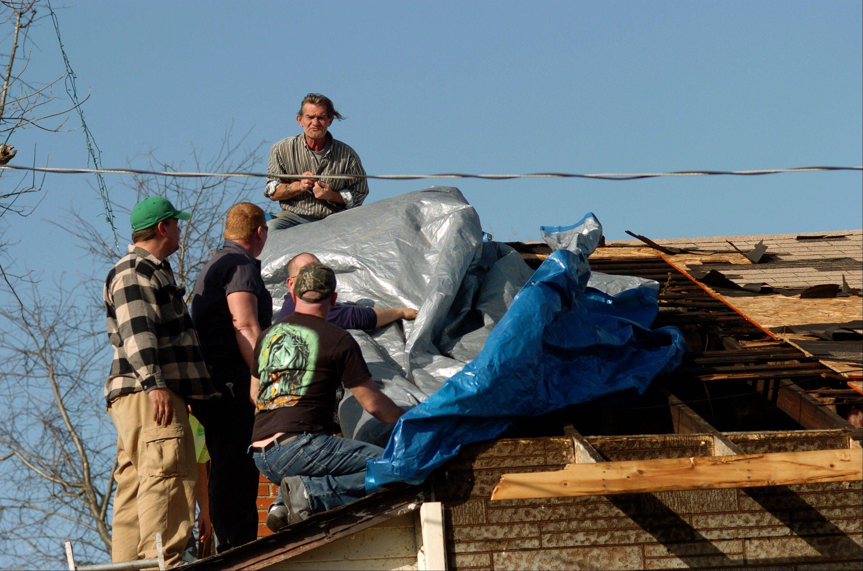 Volunteers use a tarp to cover the roof of the home of Edith Raynes, 86, in Harrisburg, Ill., Wednesday, Feb. 29, 2012. The tornado that blasted Harrisburg in southern Illinois, killing six, was an EF4, the second-highest rating given to twisters based on damage. Scientists said it was 200 yards wide with winds up to 170 mph.