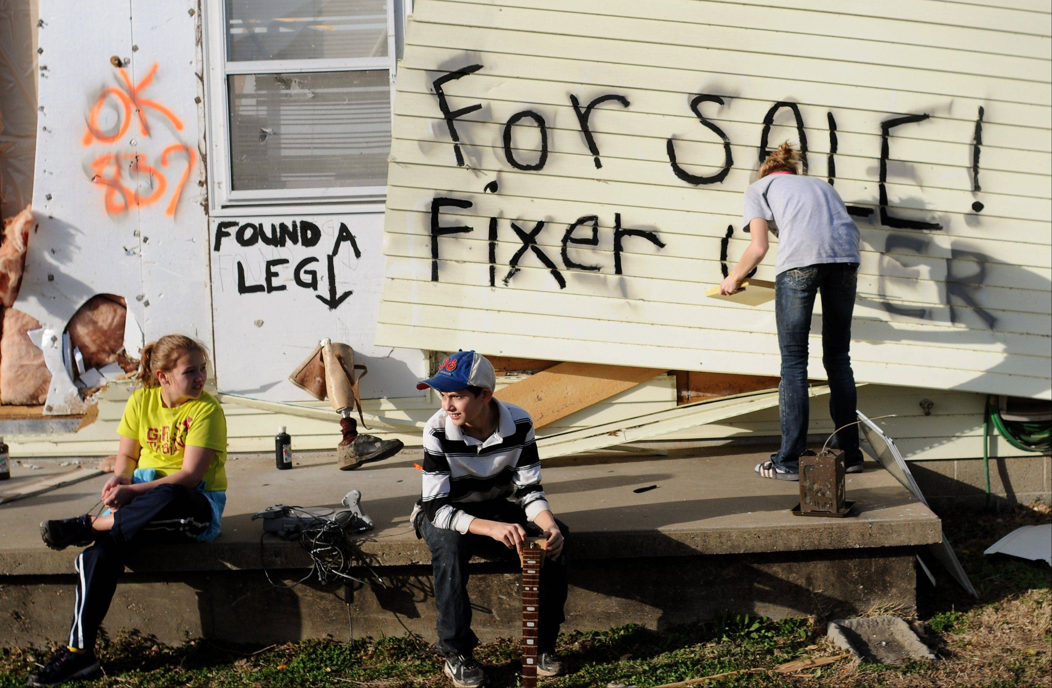 "From left, Alli Ferrell, 10, and cousin Christian Murray, 12, sit on the front porch, as Lindsey Murray, 15, of Harrisburg, Ill., paints ""for sale fixer upper"" on the side of the home of their grandmother, Sharon Murray, 61, after a tornado destroyed the house in Harrisburg, Ill., Wednesday, Feb. 29, 2012. A tornado struck the small town in southern Illinois killing 6. Murray was not at home at the time of the storm. A prosthetic leg was found among the wreckage."