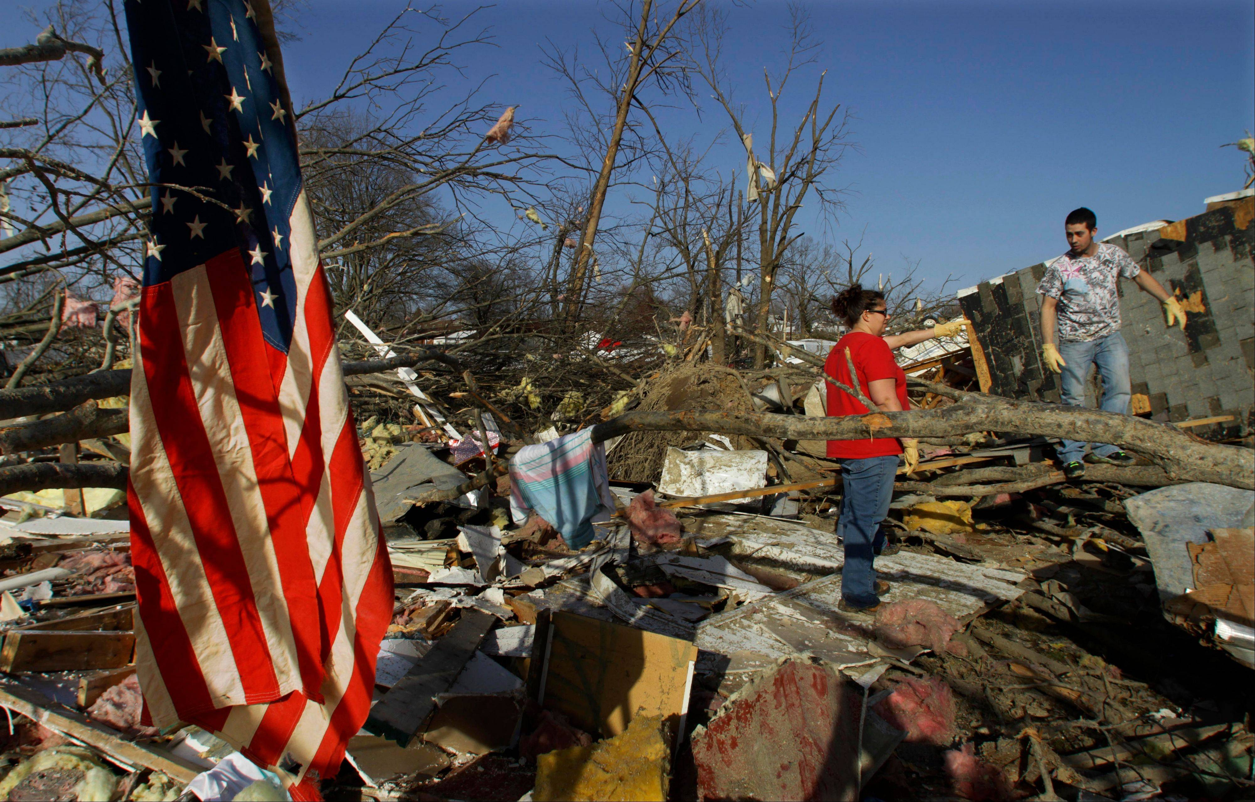 Jeff Rann, 29, right, pauses while sifting for possessions in the remains of their parents' duplex trying to salvage what he can after a tornado destroyed their parents home Wednesday, Feb. 29, 2012, in Harrisburg, Ill. Their parents were cancer survivors Randy Rann, 65, and Donna Rann. Randy died at the scene and his wife died later at a hospital.