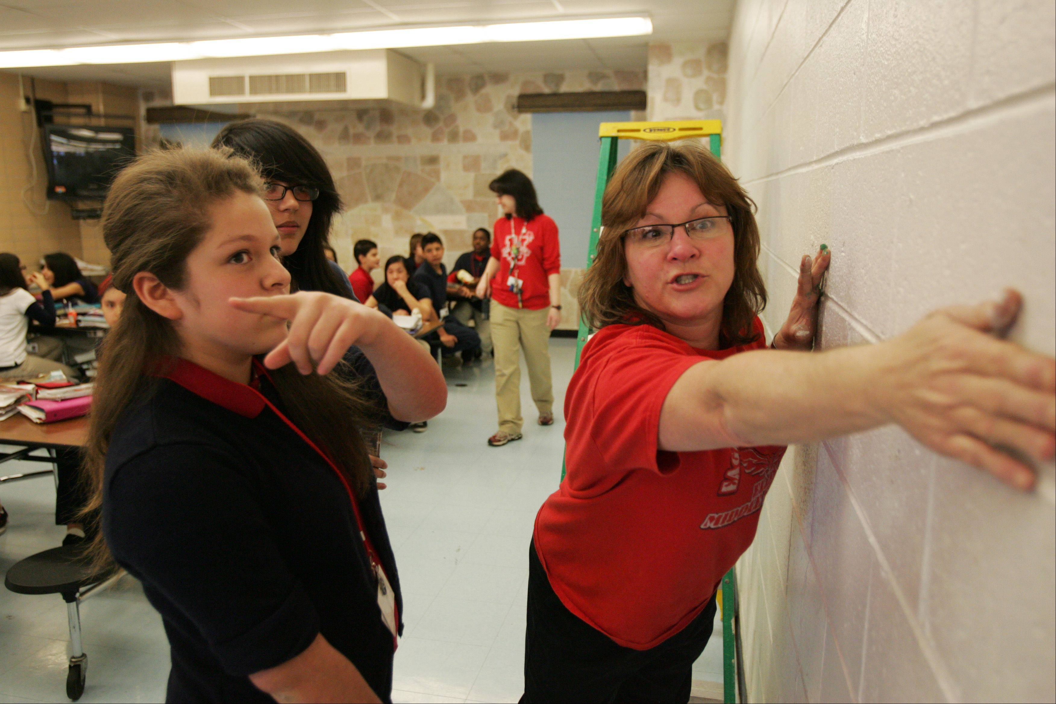 Steurer works with Ellis Middle School eighth-graders Guadalupe Hernandez, front, and Julissa Renteria as they prepare to paint a portion of the cafeteria wall.