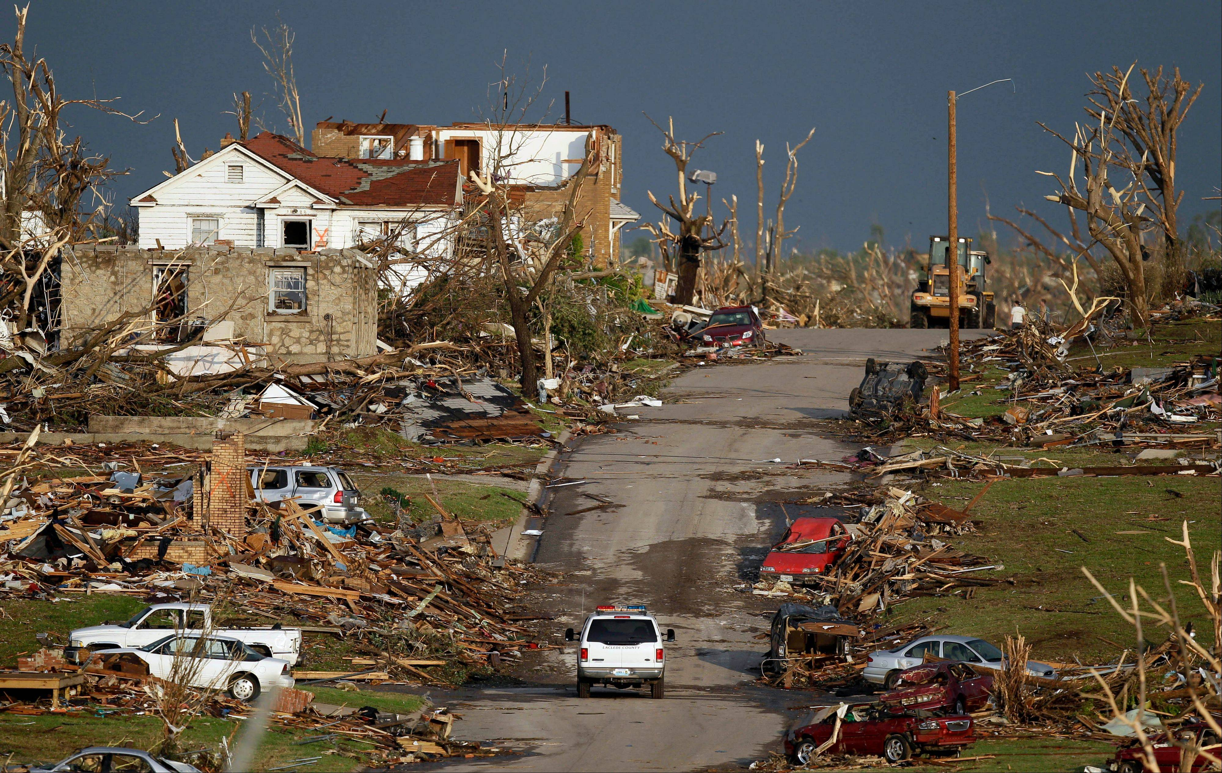 An emergency vehicle drives through a severely damaged neighborhood in Joplin, Mo., Monday, May 23, 2011. A large tornado moved through much of the city Sunday, damaging a hospital and hundreds of homes and businesses and killing at least 89 people.