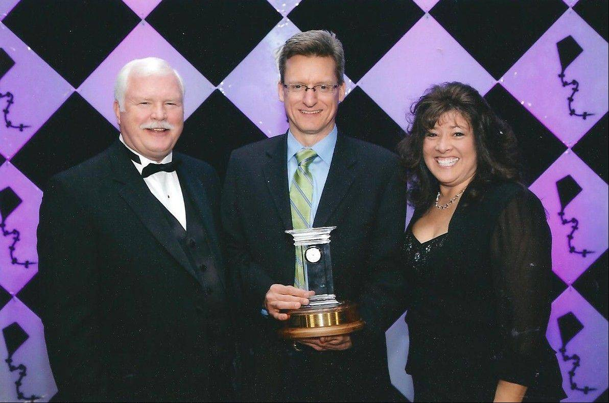 Mike Renner, center, with Peter M. Murphy and Colette Kubiesa, receives the Mike Cassidy Commissioner Community Service Award at the 2013 Illinois Association of Park Districts and the Illinois Park and Recreation Association's Soaring to New Heights Conference.