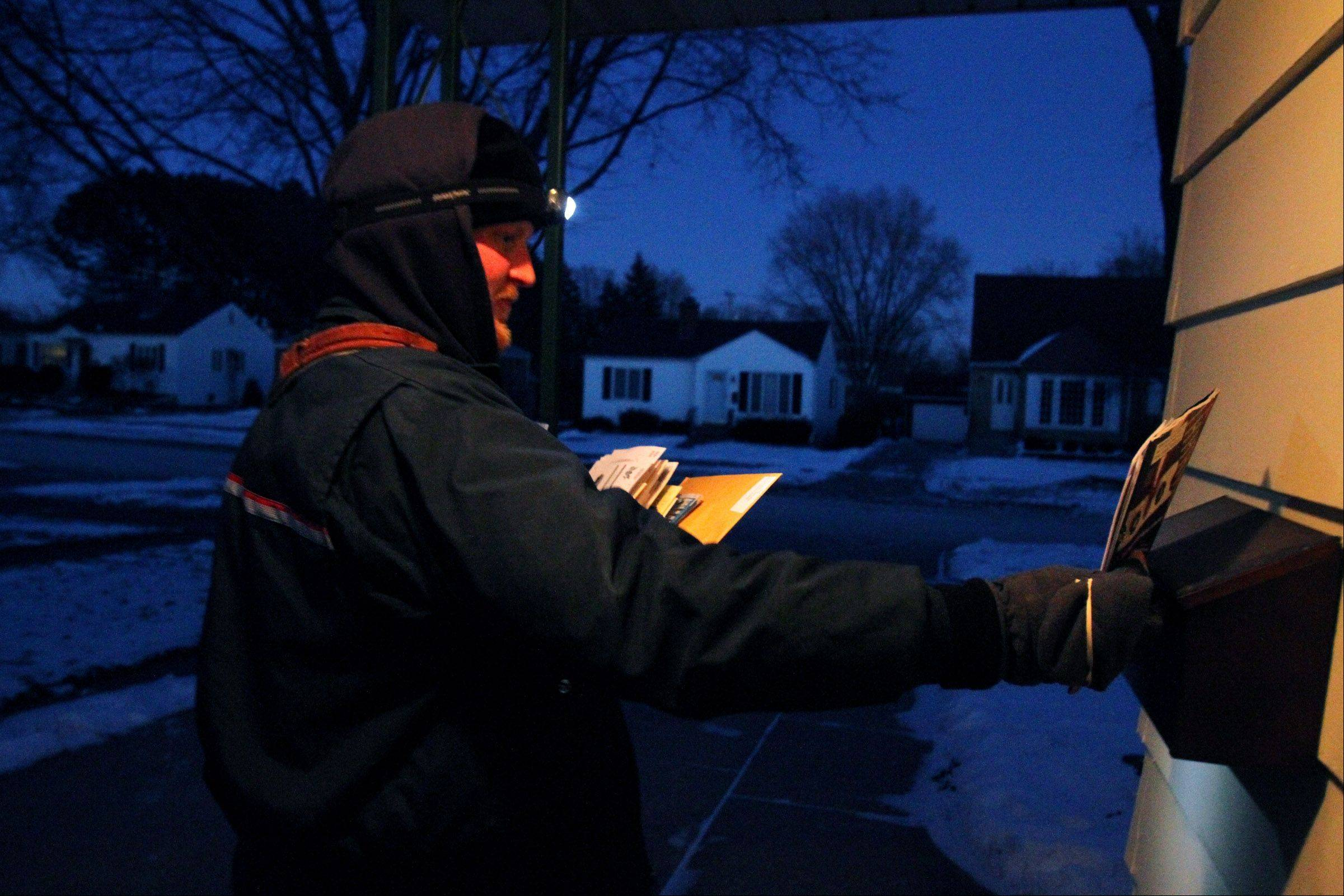 Mount Prospect postal carrier Jacob Tagge wears a headlamp while delivering mail to homes just east of the Mount Prospect Post Office between 5 and 6 p.m. on a winter day.