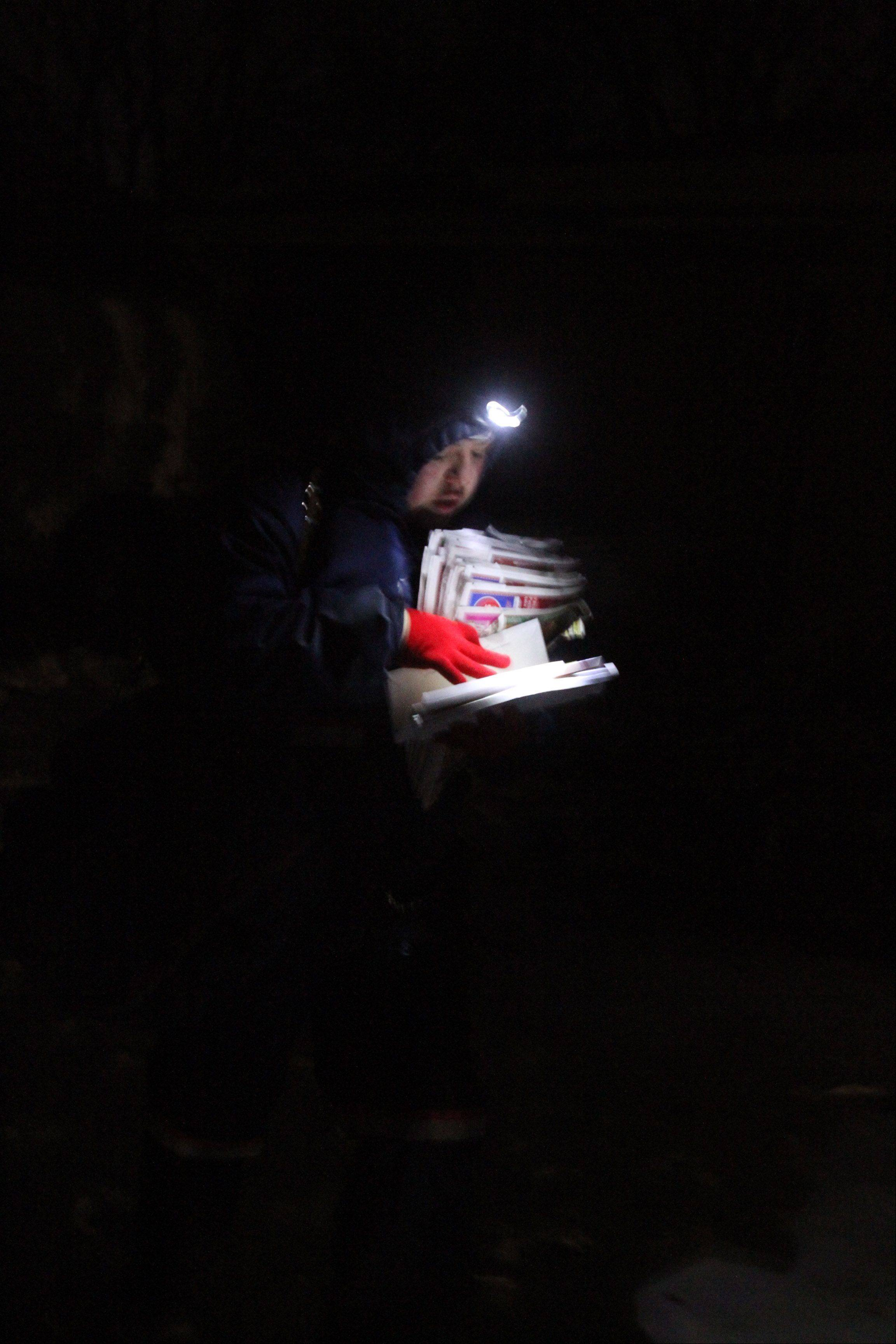 Mount Prospect postal carrier Lidia Garcia looks at addresses using a headlamp as she delivers mail to homes just southeast of the Mount Prospect Post Office between 5 and 6 p.m. on a winter day.