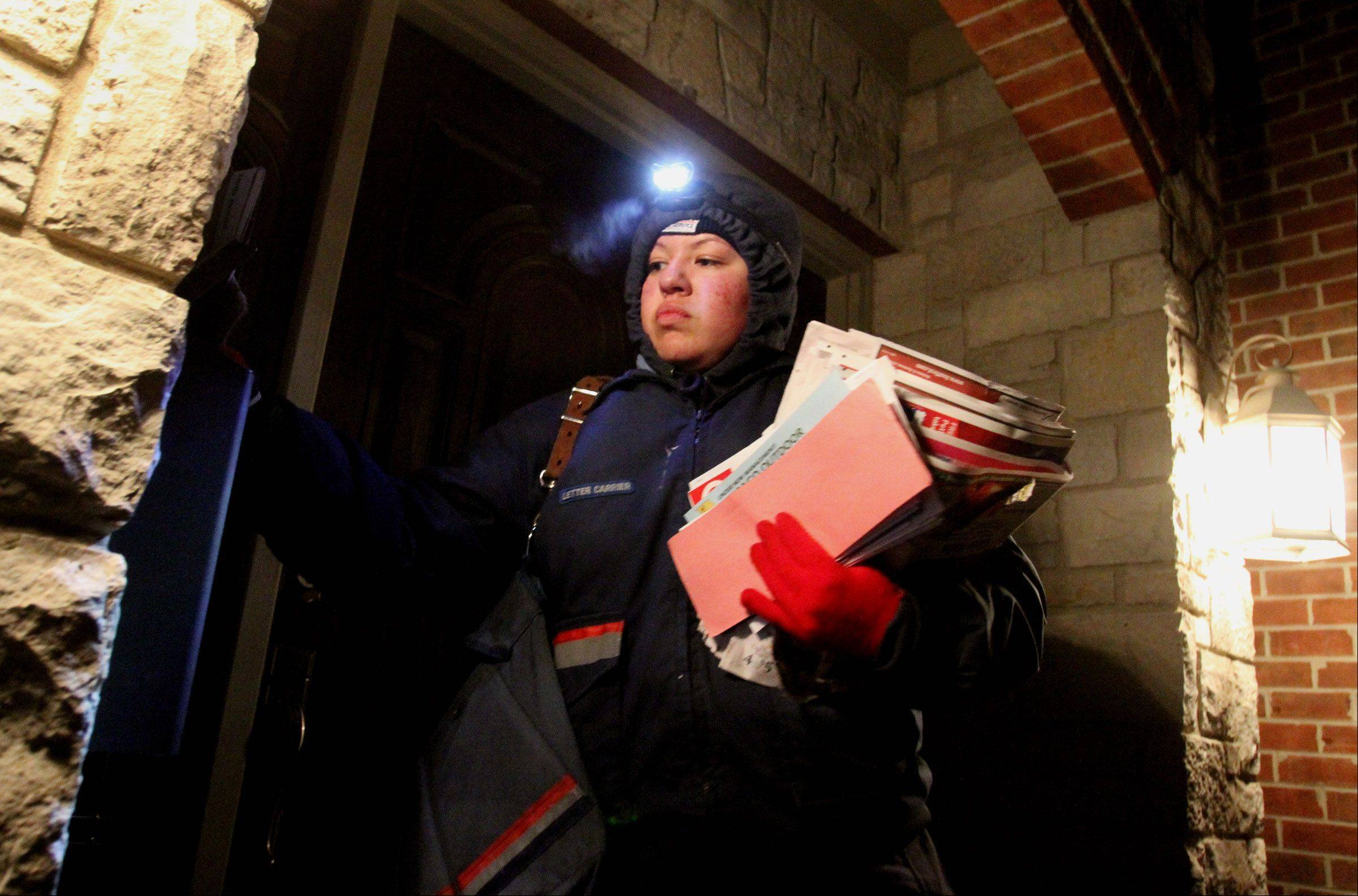 Mount Prospect postal carrier Lidia Garcia looks at addresses using a headlamp as she delivers mail to homes just southeast of the post office between 5 and 6 p.m. on a winter day.
