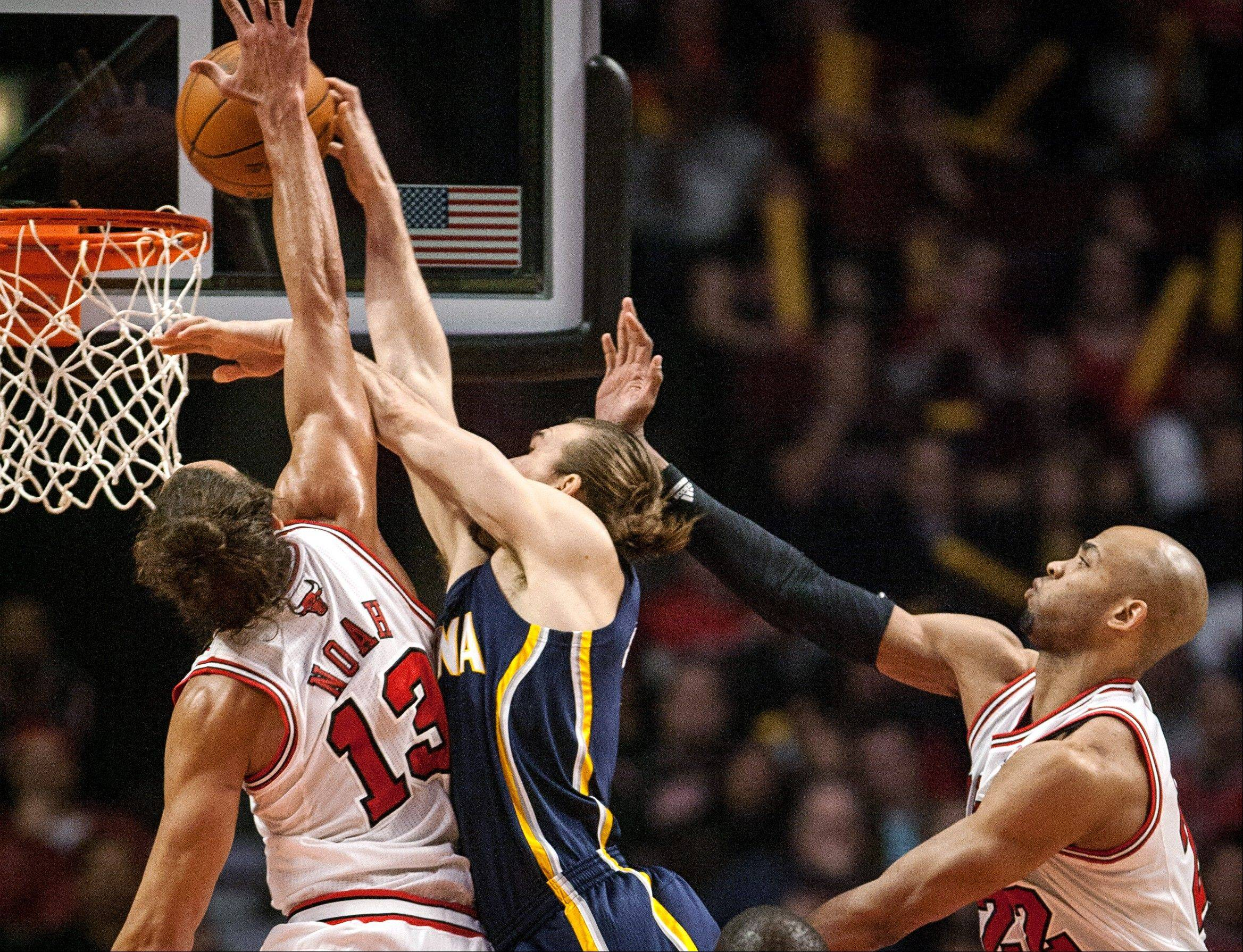 Chicago Bulls' Joakim Noah blocks a shot by the Indiana Pacers' Lou Admundson and is called for a foul during the first quarter of an NBA basketball game in Chicago on Monday, March 5, 2012. Bulls' Taj Gibson is at right.