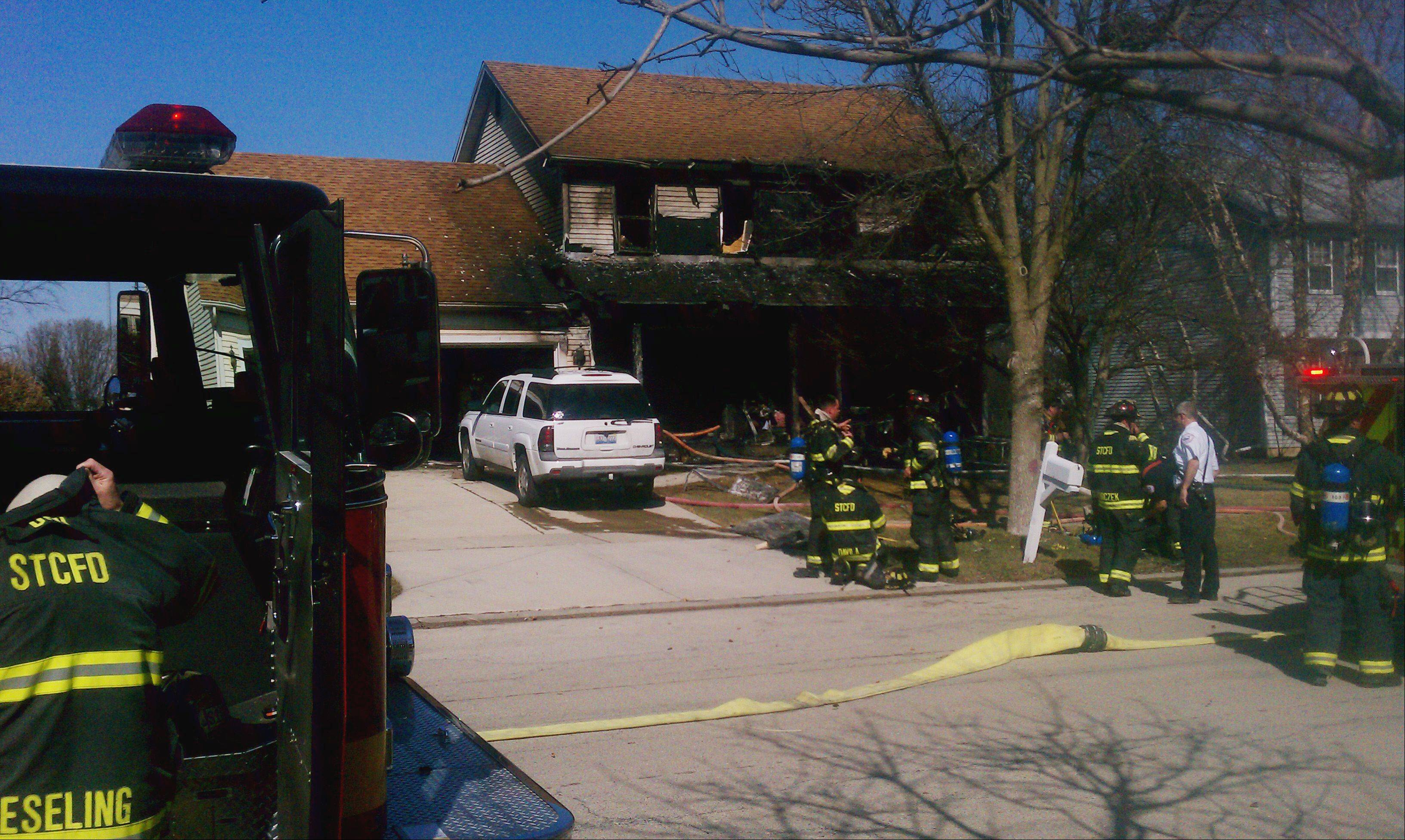 Firefighters work the scene of a structure fire in the 2000 block of Cambridge Drive Tuesday afternoon in St. Charles.