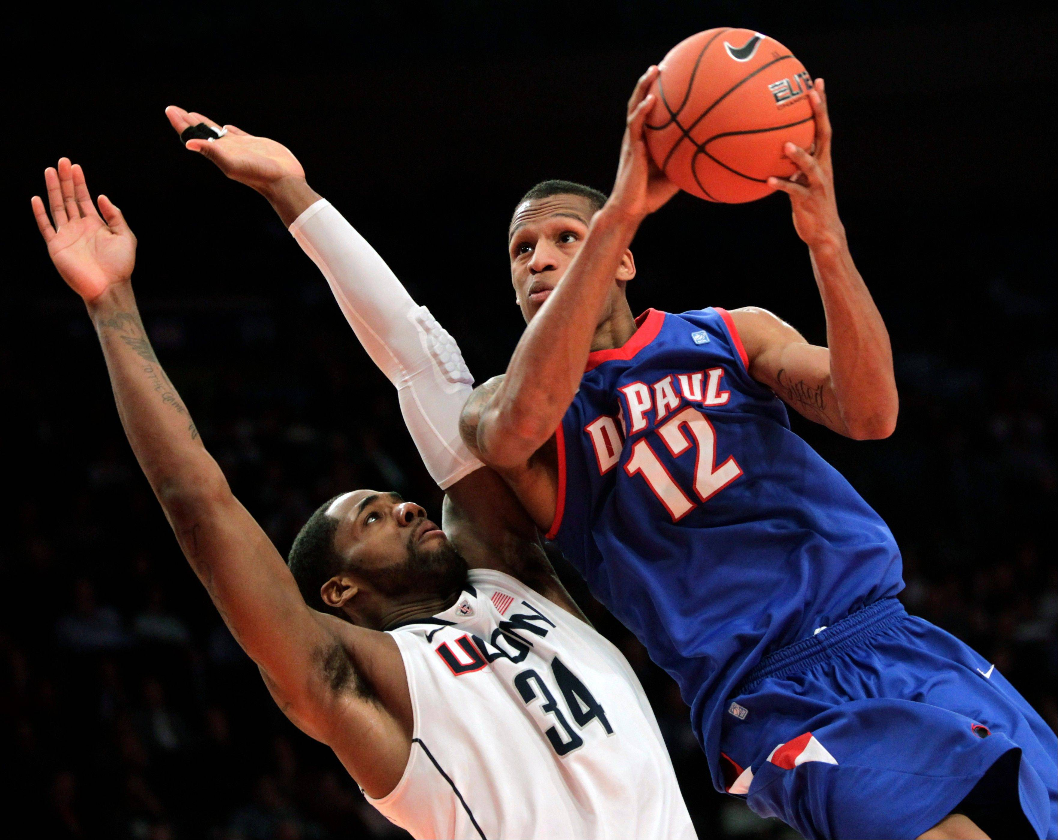 DePaul's Cleveland Melvin tries to score past Connecticut's Alex Oriakhi Tuesday during the first round of the Big East NCAA college basketball conference tournament game.
