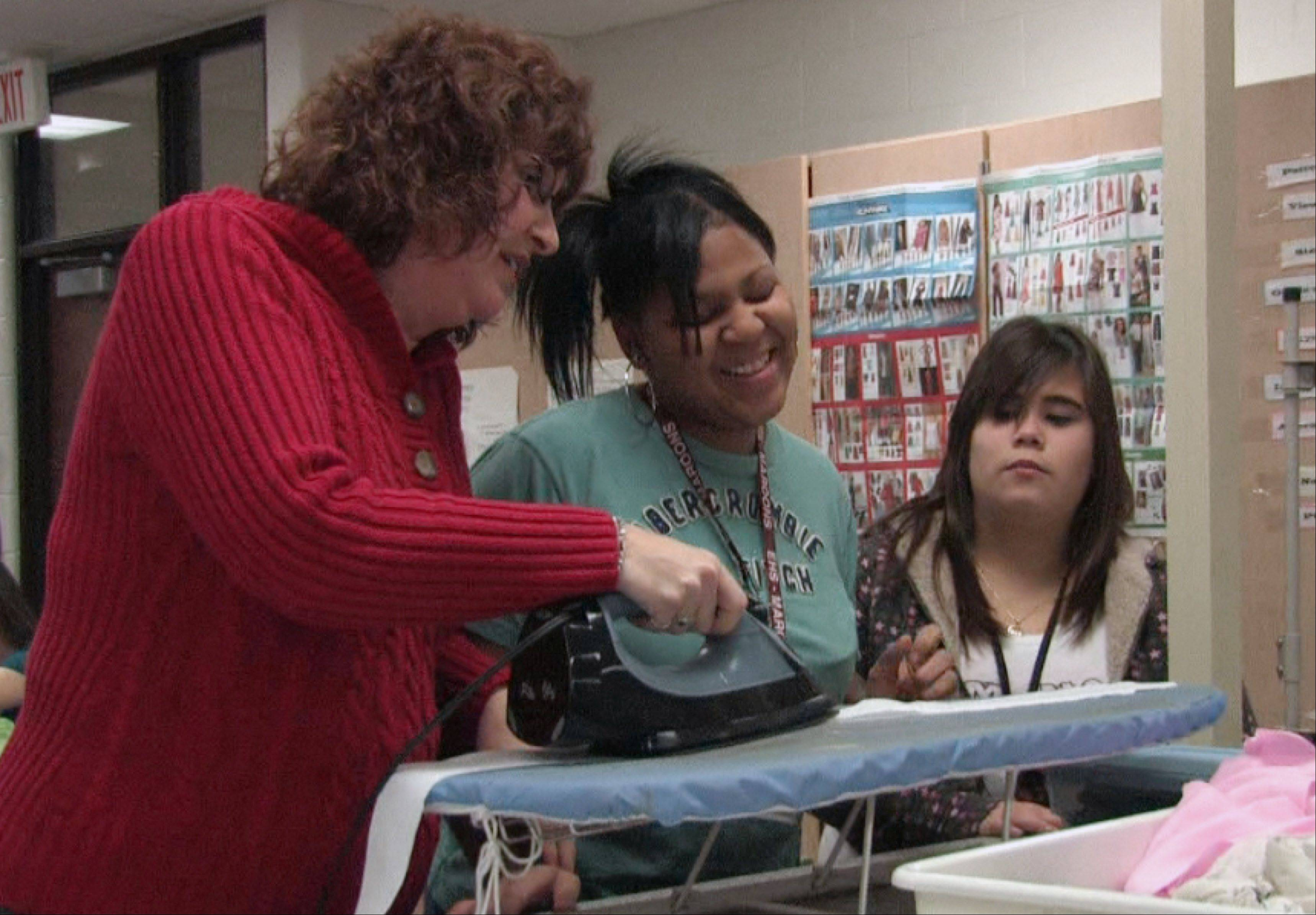 Back teaching at Elgin High School after her recovery, Carolyn Gilbert works with students in home economics class.