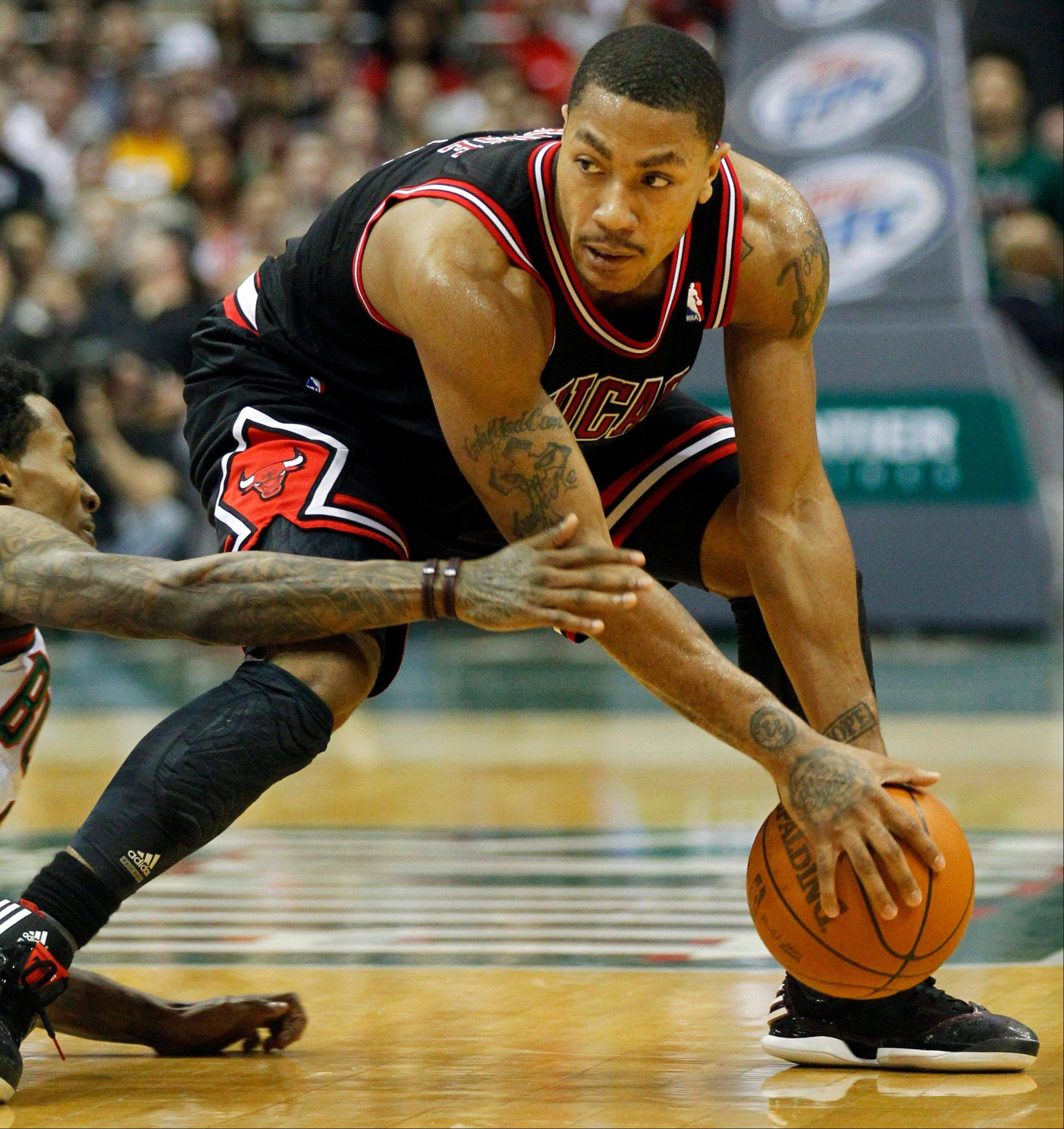 Derrick Rose picks up a loose ball ahead of the Bucks' Brandon Jennings during the first half Wednesday in Milwaukee