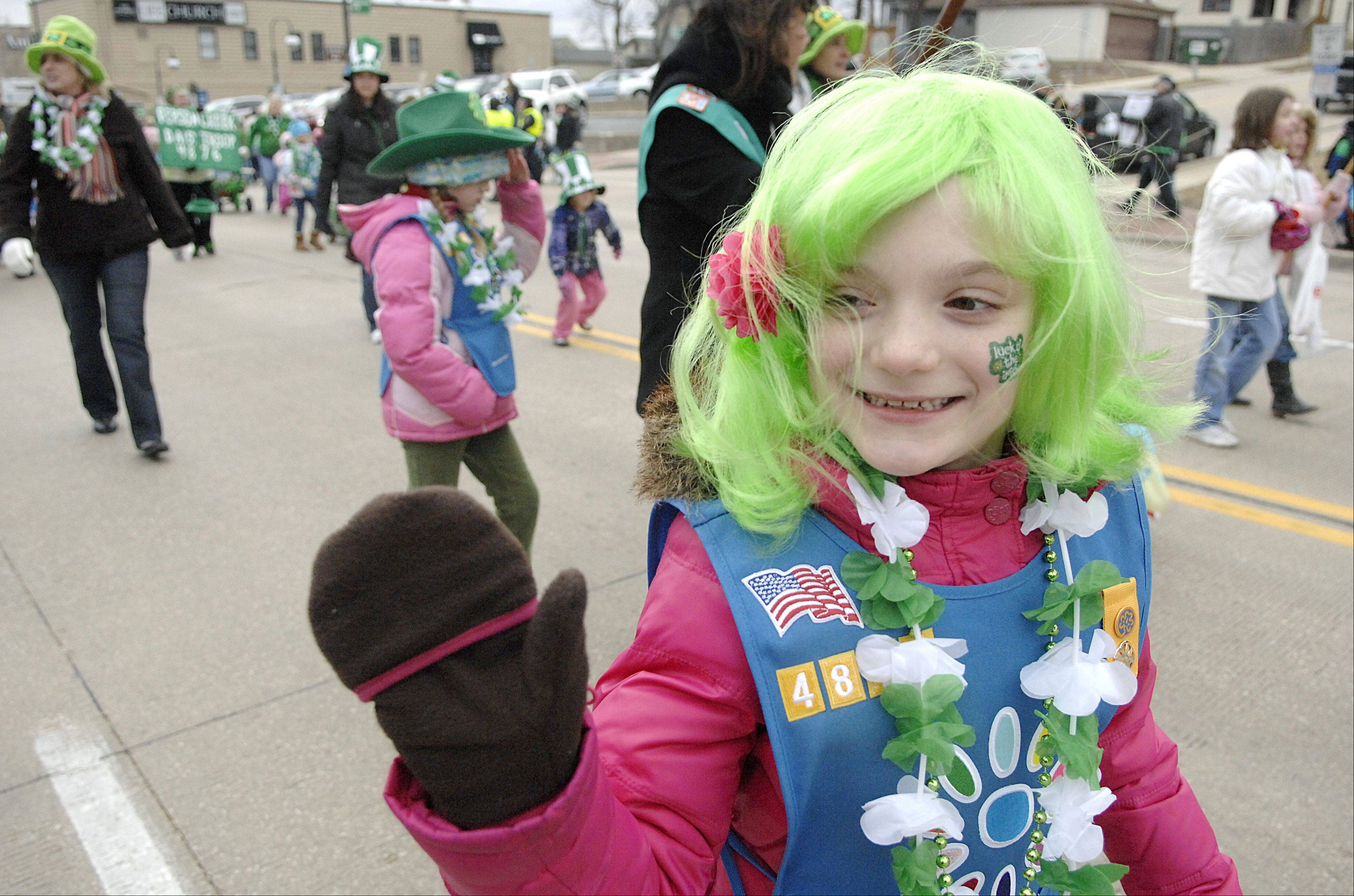 Madison Schiffer, 7, of St. Charles waves to the crowds watching the St. Patrick's Day parade march through downtown St. Charles last year. Madison and her fellow Daisy Troop 4879 from Ferson Creek Elementary School walked in the annual parade.