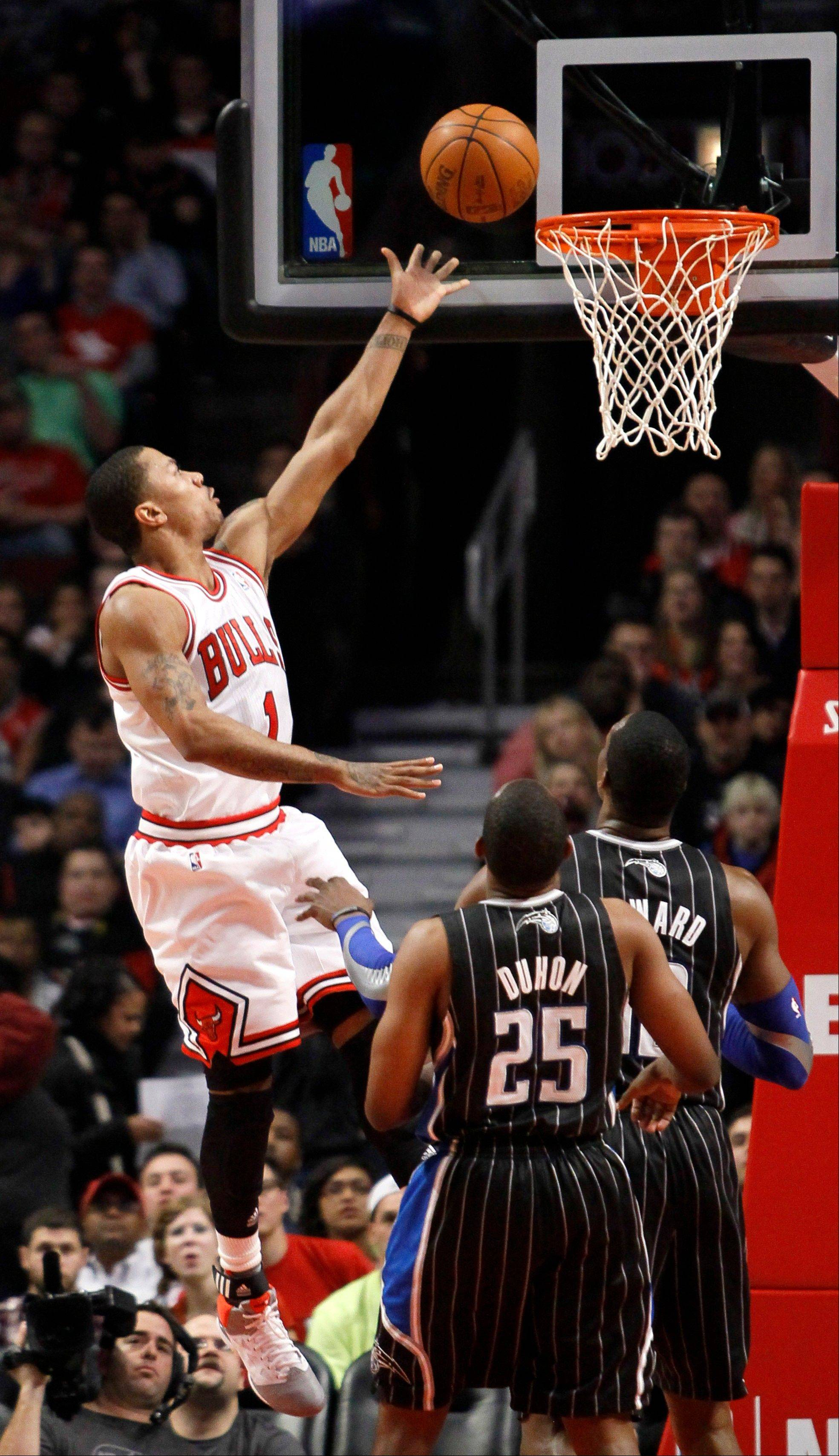 Chicago Bulls guard Derrick Rose (1) drives to the basket past Orlando Magic's Chris Duhon and Dwight Howard during the first half of an NBA basketball game Thursday, March 8, 2012, in Chicago.