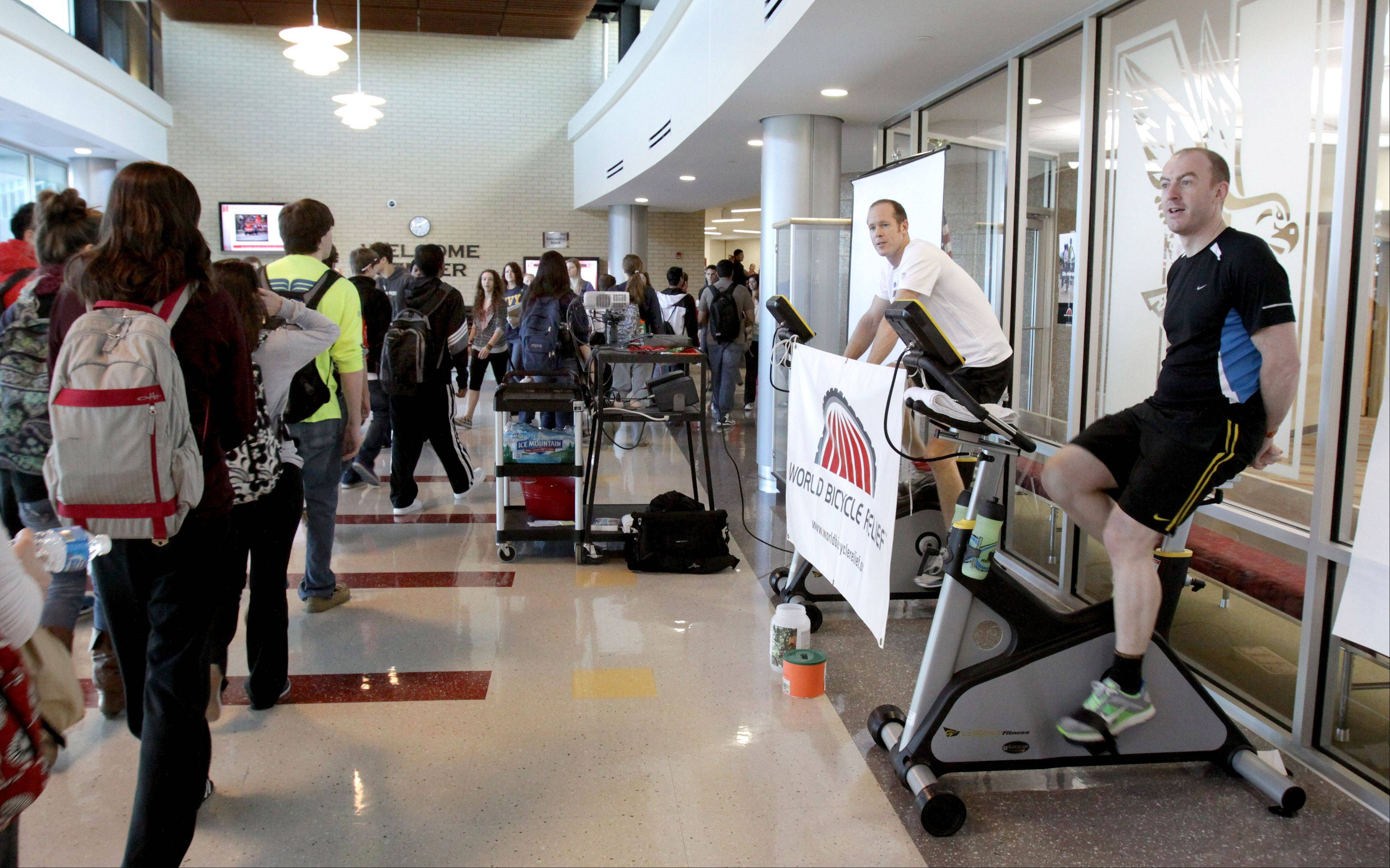 Teachers Neil Duncan, left, and Marc O'Shea pedal stationary bikes Friday at Naperville Central High School to raise money for World Bicycle Relief.