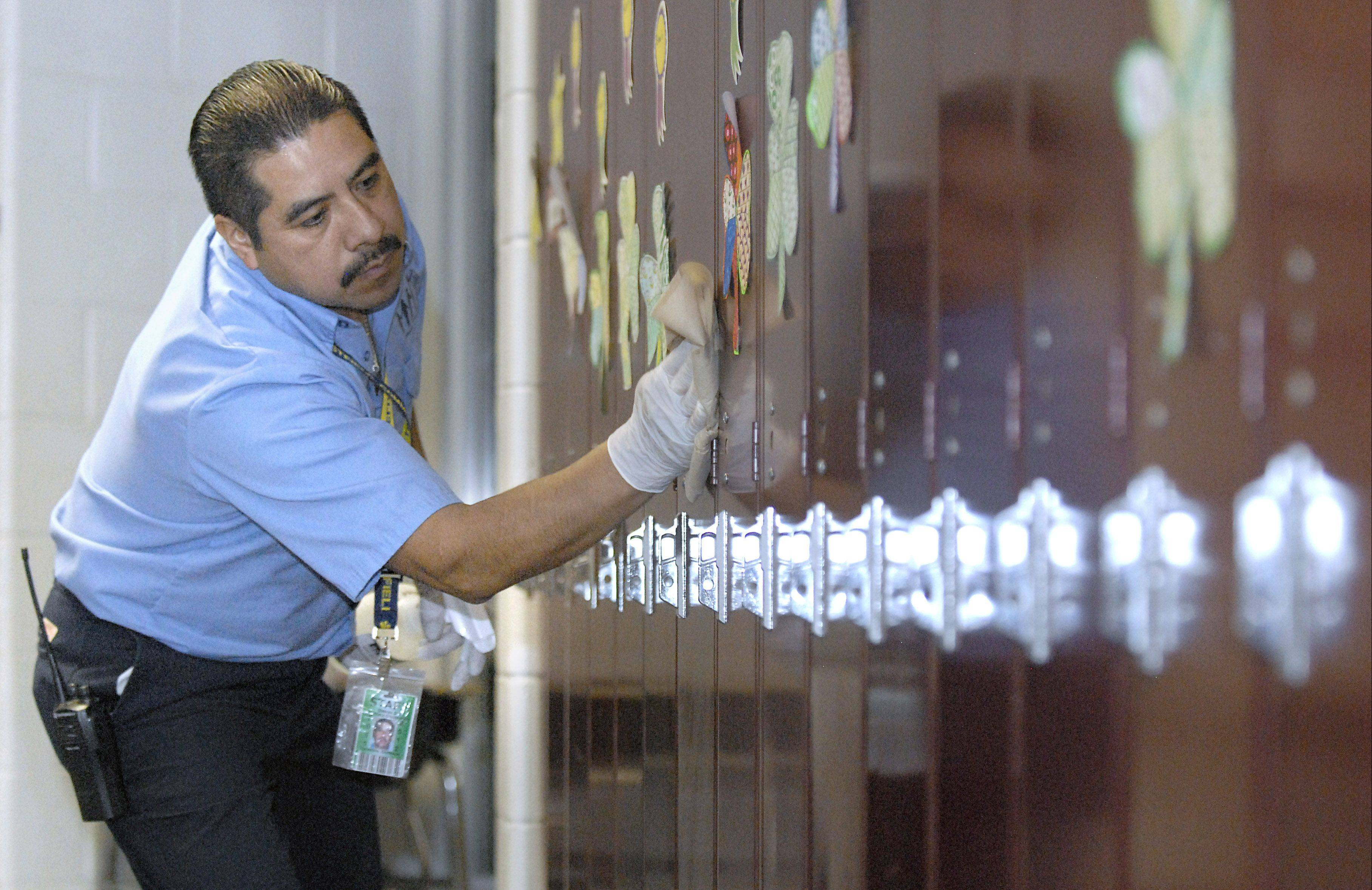 Head custodian Teles Contreras disinfects locker surfaces and handles Friday at Westfield Community School in Algonquin.