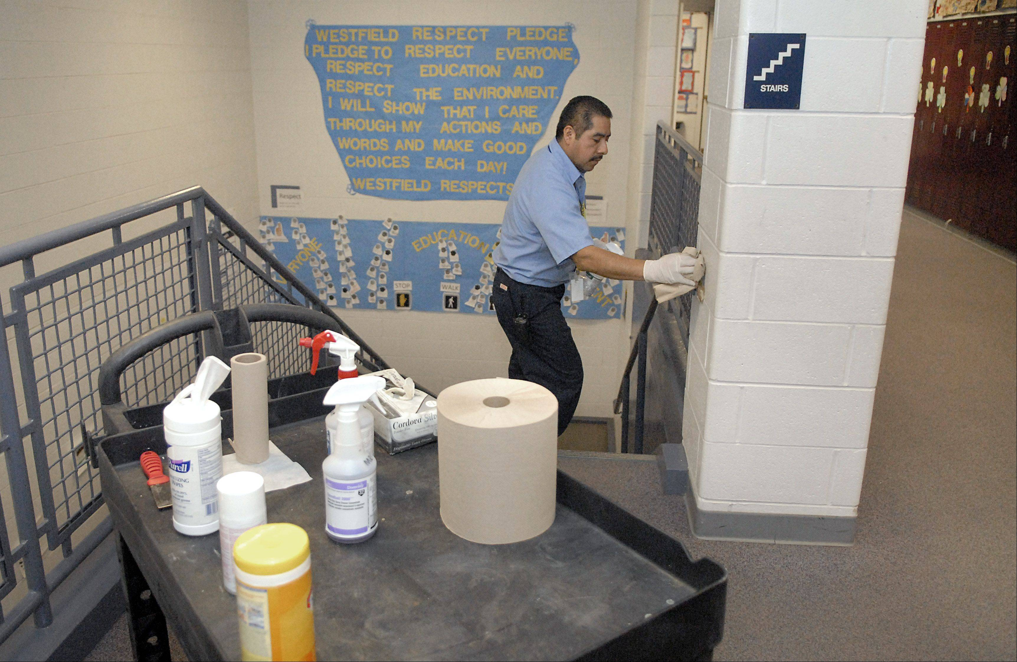 Head custodian Teles Contreras disinfects locker surfaces and handles Friday at Westfield Community School in Algonquin. Norovirus is raging through the school with more than half of the school's elementary population out sick on Friday. Within four hours of cleaning on Friday, Contreras had already gone through three bottles of the disinfectant.