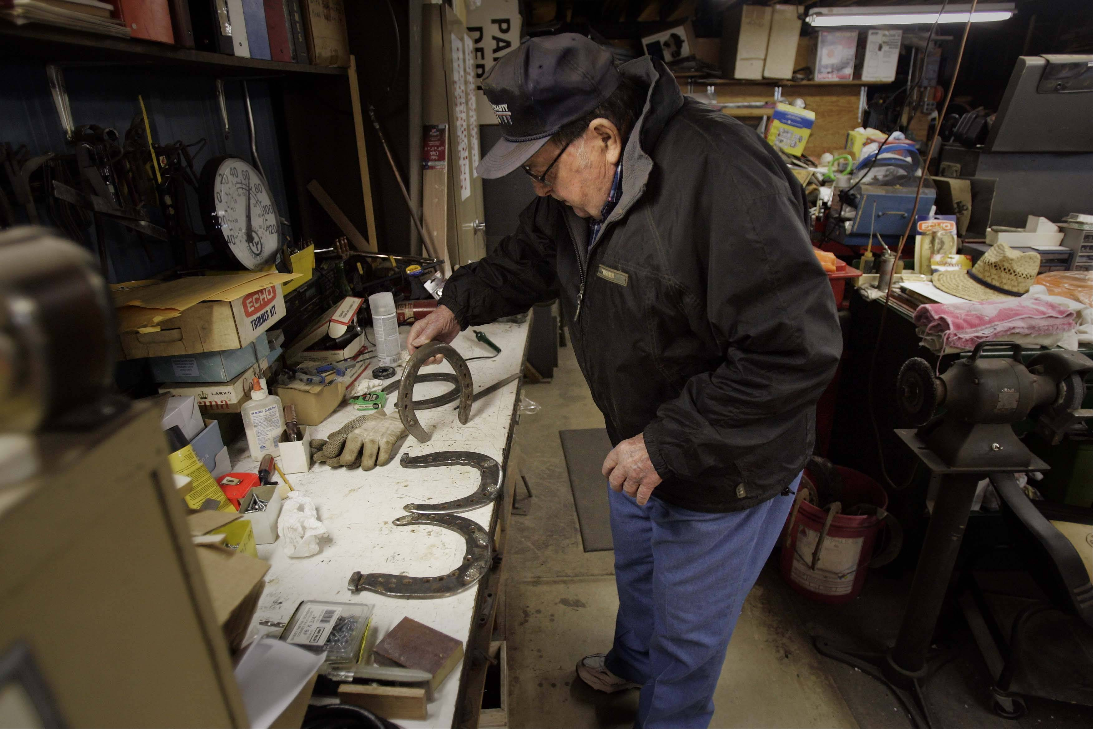 Melvin Peterson, 91, of St. Charles, works almost daily at the Wasco Blacksmith Shop, and here spends time cleaning special horseshoes that were used on Clydesdale horses.