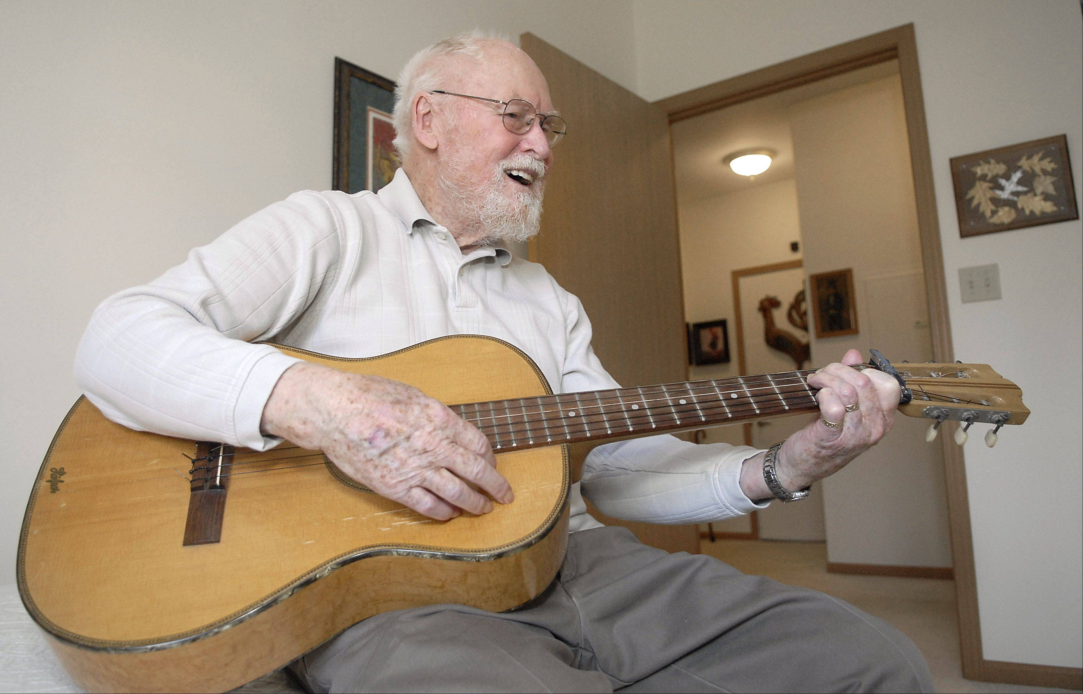 Ken Page plays his guitar in his Elgin home. Page worked for Sears throughout Latin America for many years. Playing the guitar, cuatro and dulcimer were a huge part of his life until tremors in his hands made it hard to play.