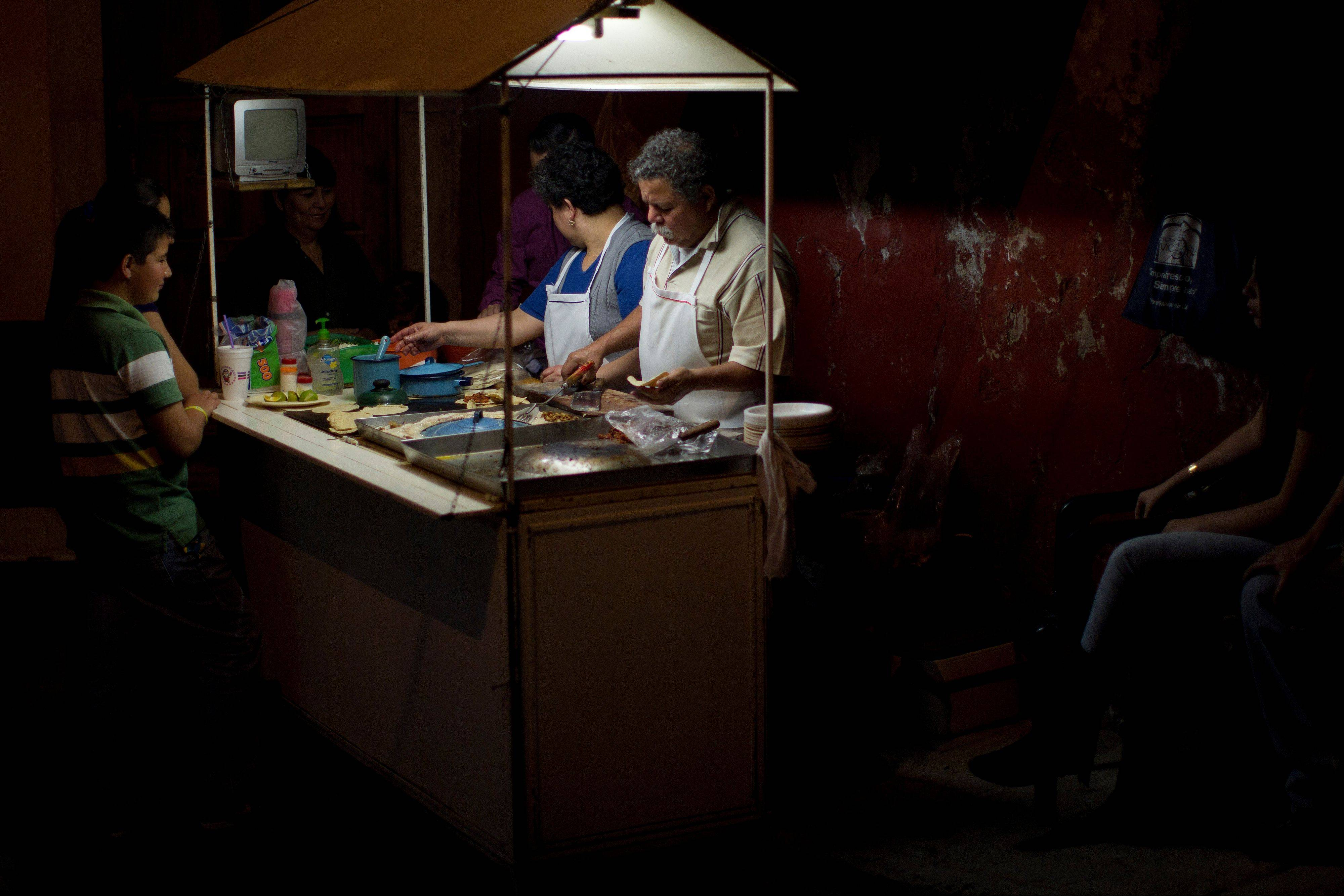 Luisa and Antonio Olmos serve costumers at their 26-year-old taco stand in a passageway at night.