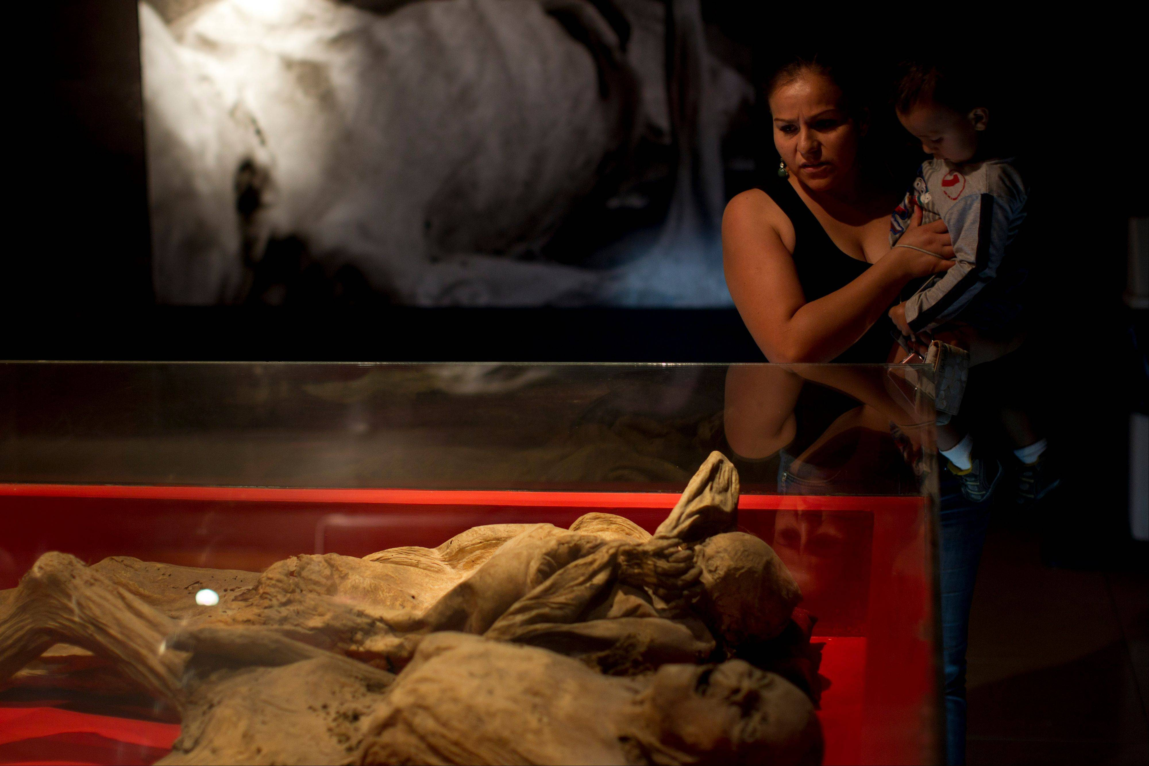 A woman carrying a child looks at mummies at the Mummy Museum in Guanajuato.