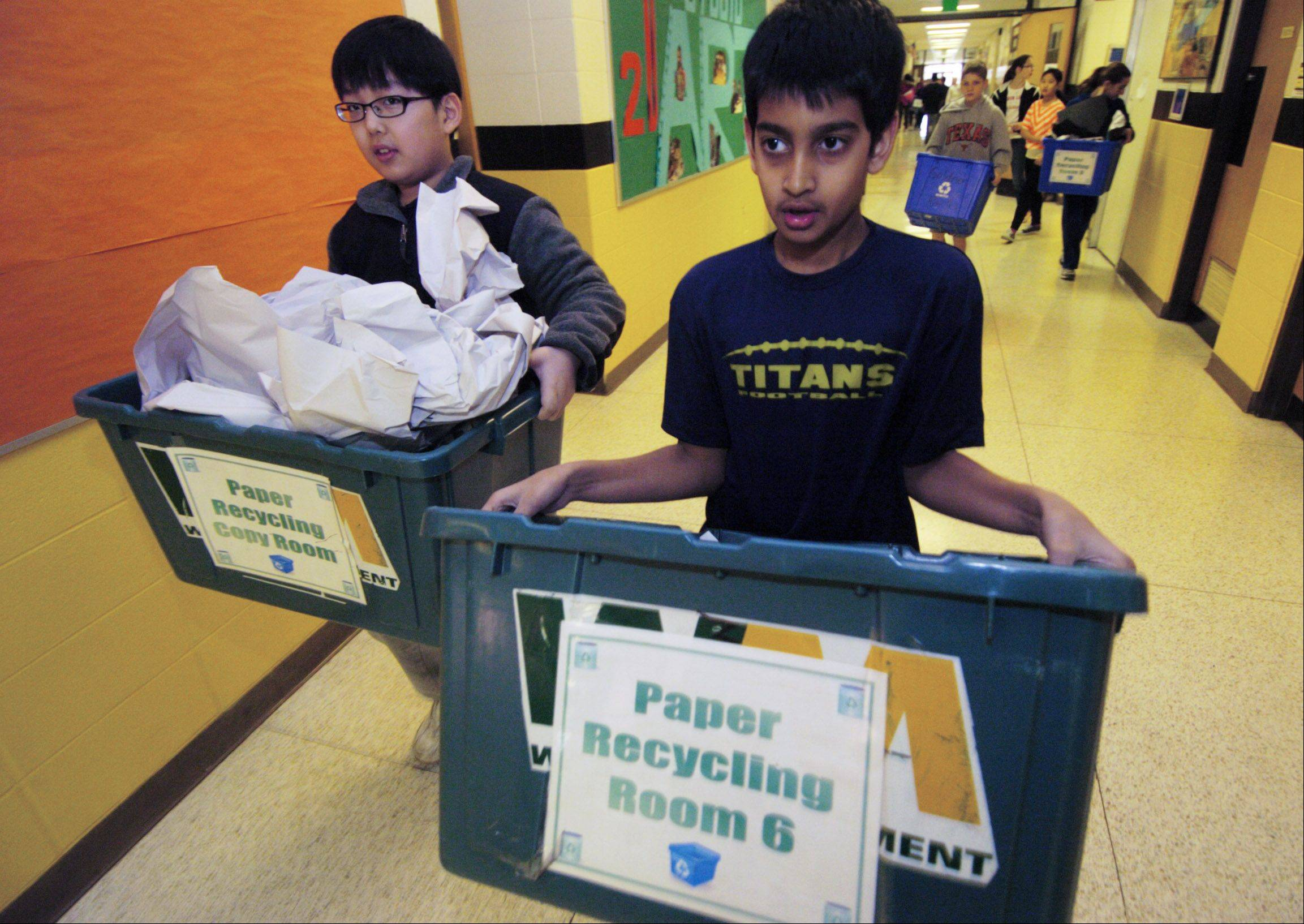 Sixth-graders Patrick An, left, and Dhruv Patel carry recycling bins from classrooms as part of their service learning project at Field Middle School in Northbrook.