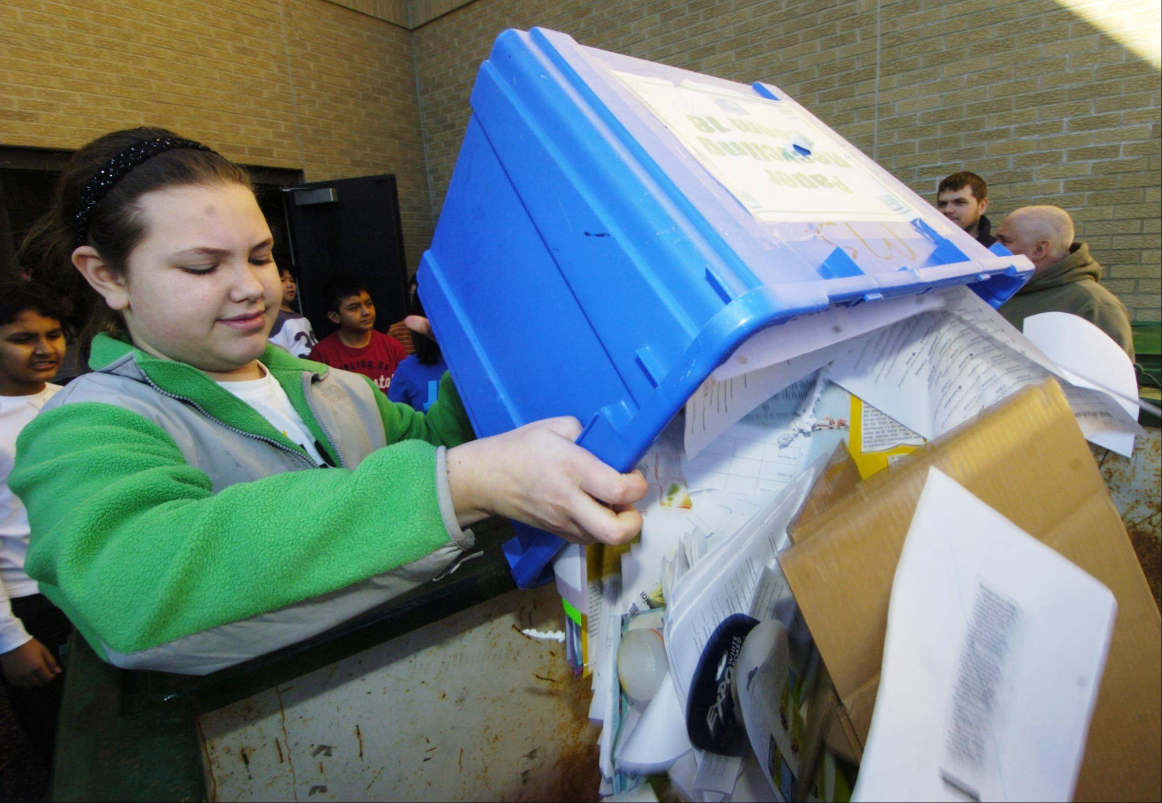 Michelle Anderson unloads a recycling bin from a classroom at Field Middle School in Northbrook.