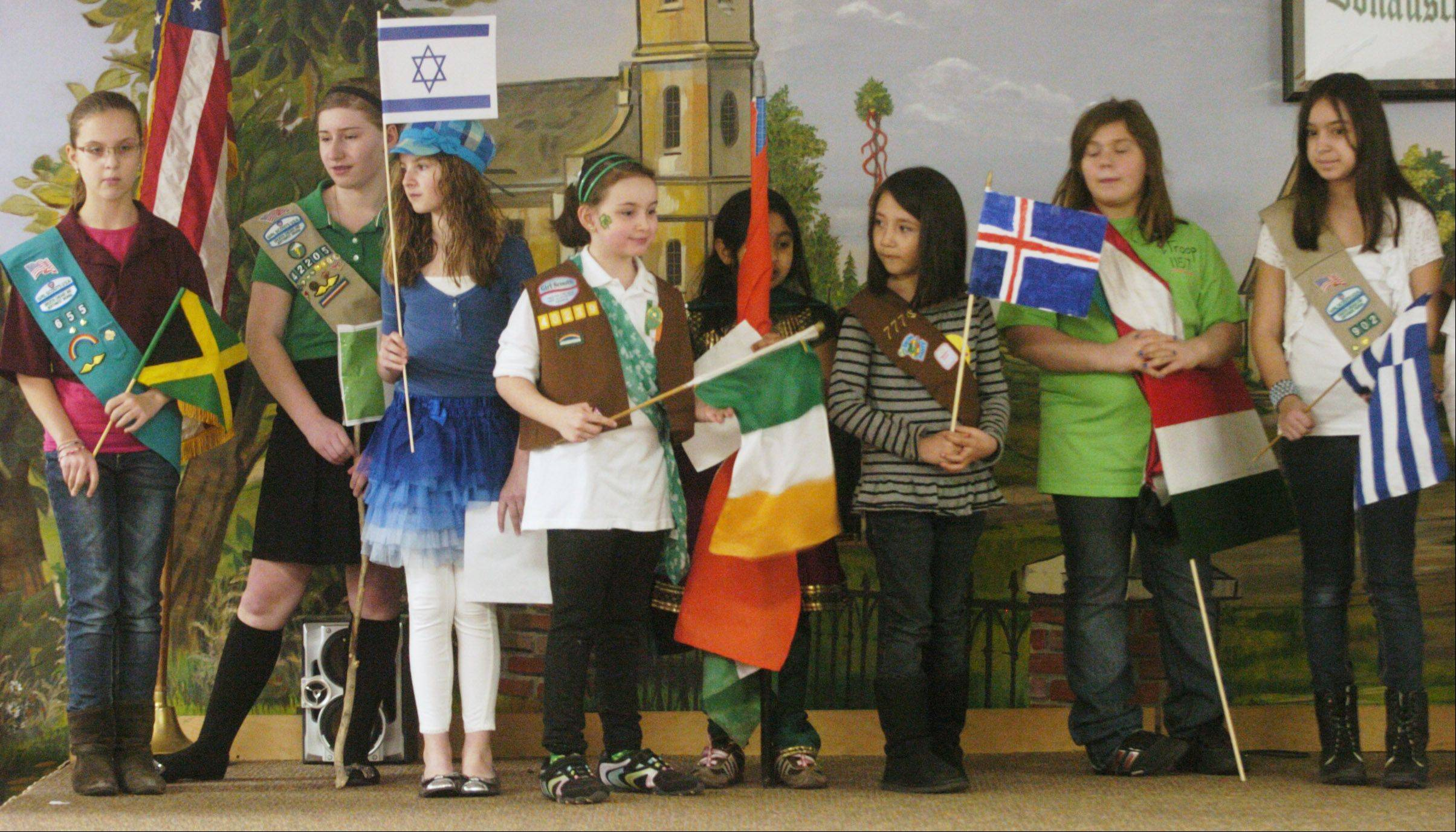 Scouts line up to present the flags of 24 nations during Girl Scouts World Thinking Day held last week at the Society of the Dunabe Swabians in Des Plaines. The Girl Scouts mark their 100th anniversary today.