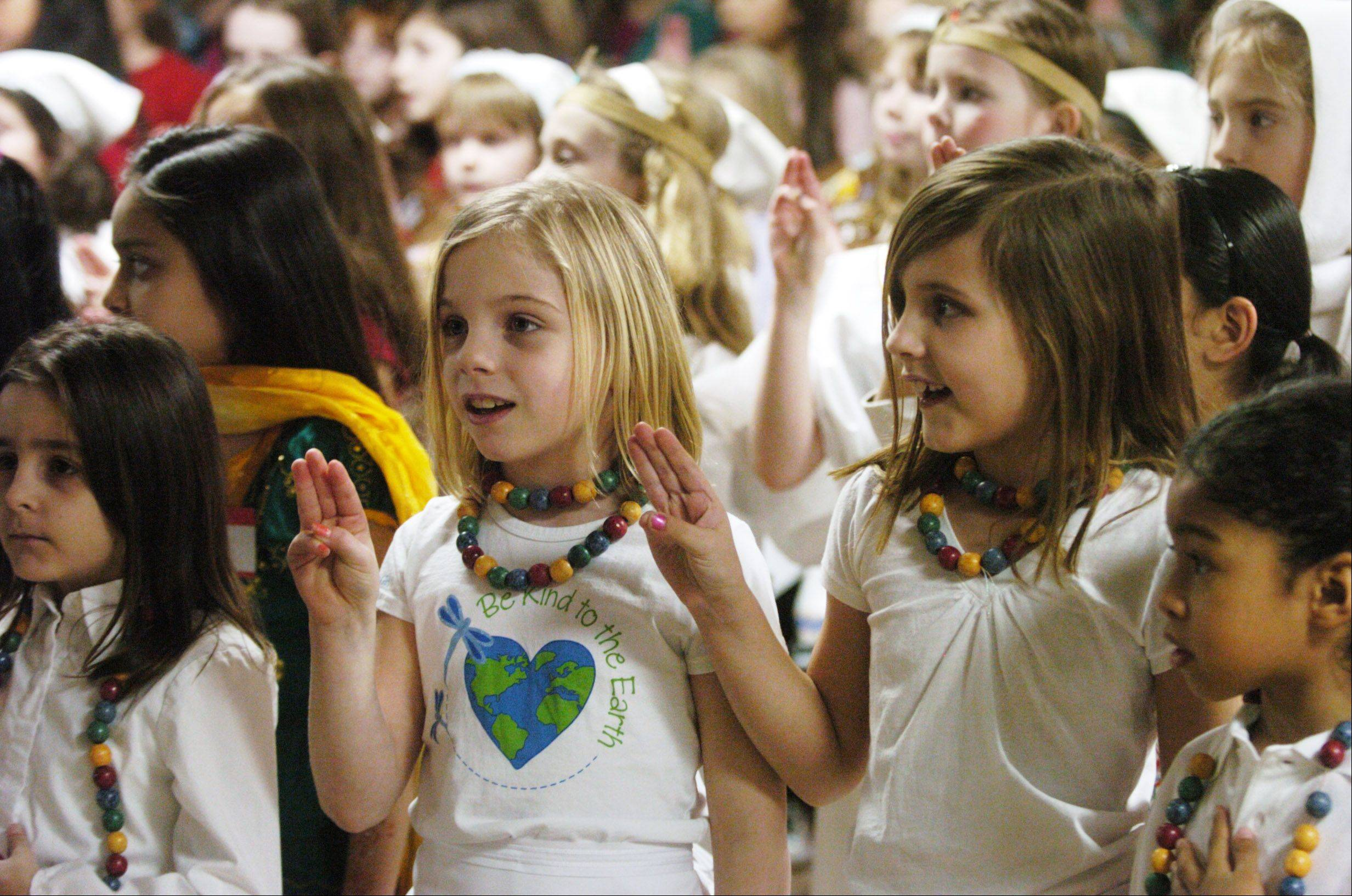 Gabriela Zabiegaj, 7, and Bailey Constock, 7, both of Mount Prospect and Daisy Troop 41735, recite the Girl Scout Promise during Girl Scouts World Thinking Day held earlier this month at the Society of the Danube Swabians in Des Plaines. The Girl Scouts mark their 100th anniversary today.