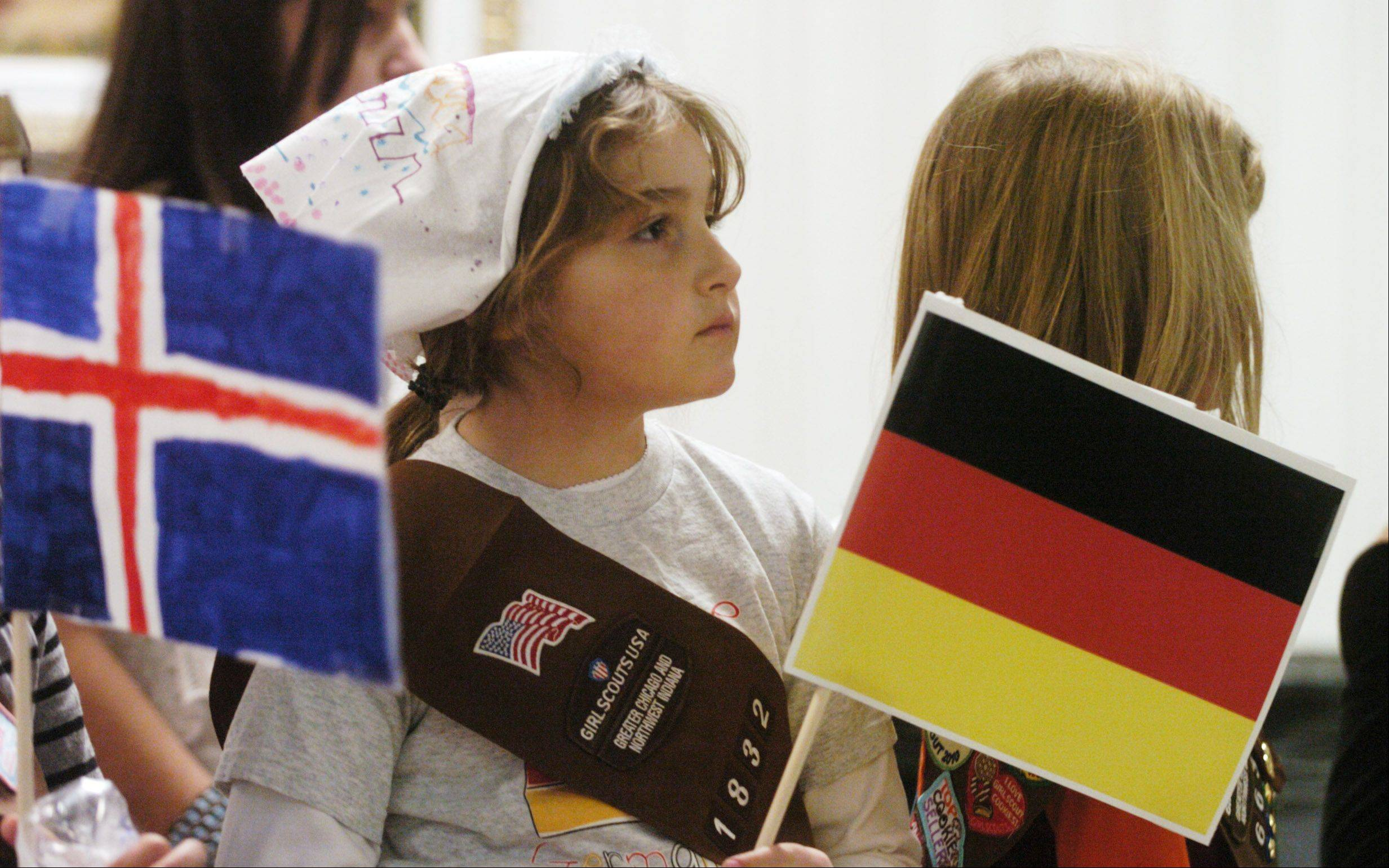 Alexandra Krieger, 7, of Troop 1832, holds the German flag during Girl Scouts World Thinking Day held earlier this month at the Society of the Danube Swabians in Des Plaines. The Girl Scouts mark their 100th anniversary today.