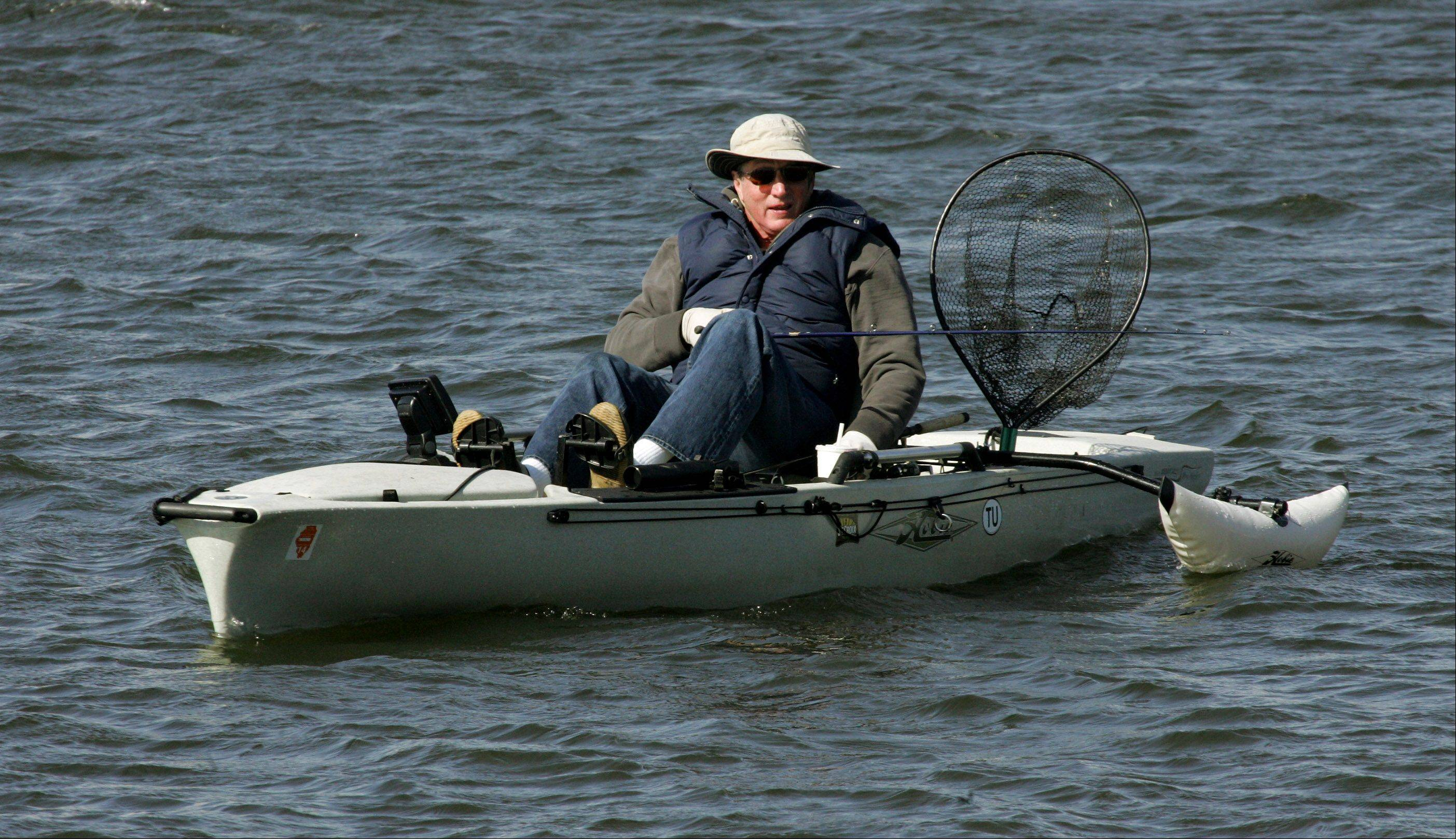 Grayslake resident Ken Haney paddles his way against high winds Tuesday as he enjoys the warm weather by fishing on a pond in Prairie Crossing.