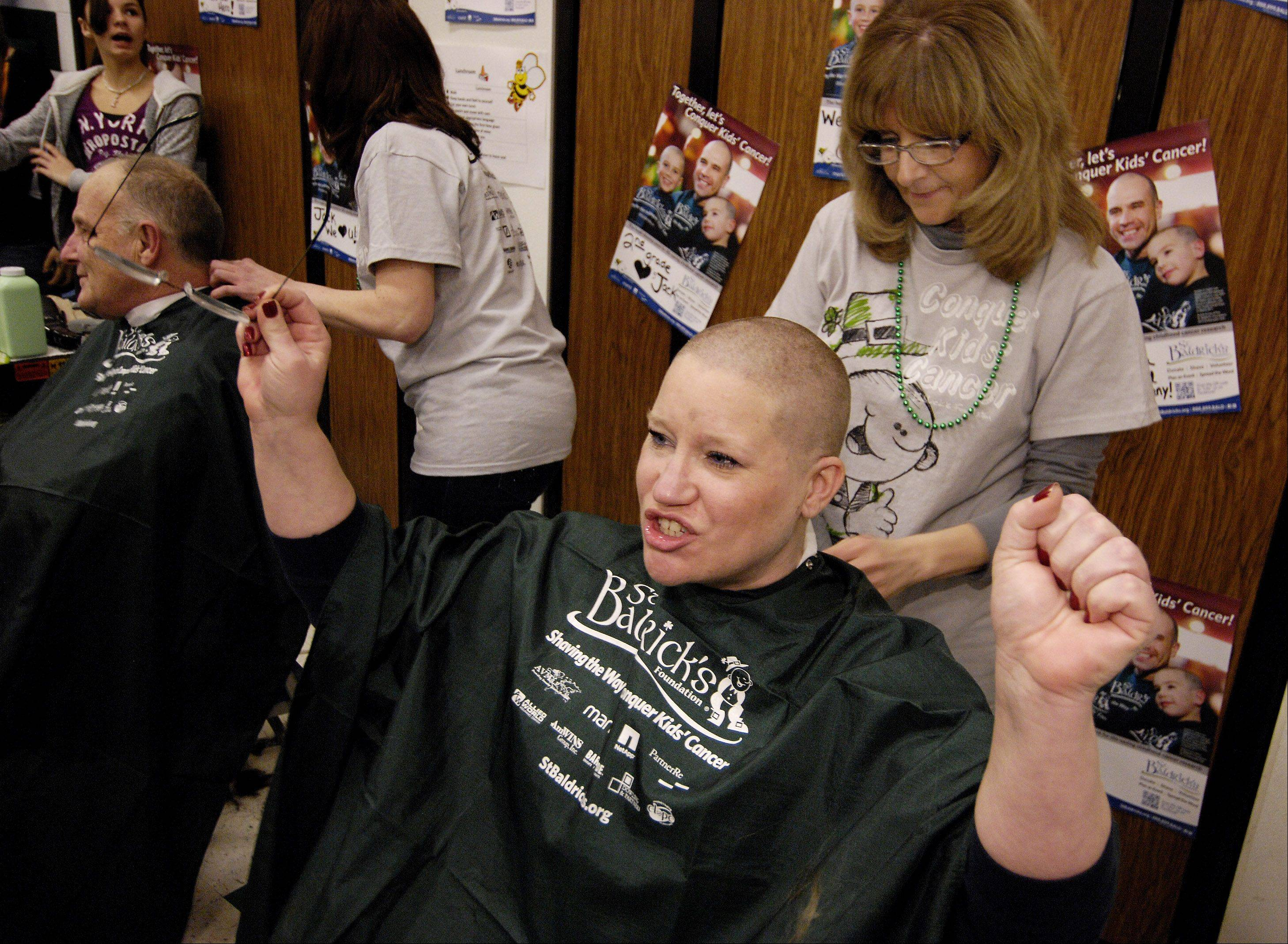 Laurie Evans of Elmhurst celebrates having her head shaved by Karen Monaco, during a St. Baldrick's fundraiser at Evergreen School in Carol Stream, for second grader Jack O'Donoghue who has Burkitt's lymphoma, a non Hodgkin's cancer of the lymphatic system, Sunday.