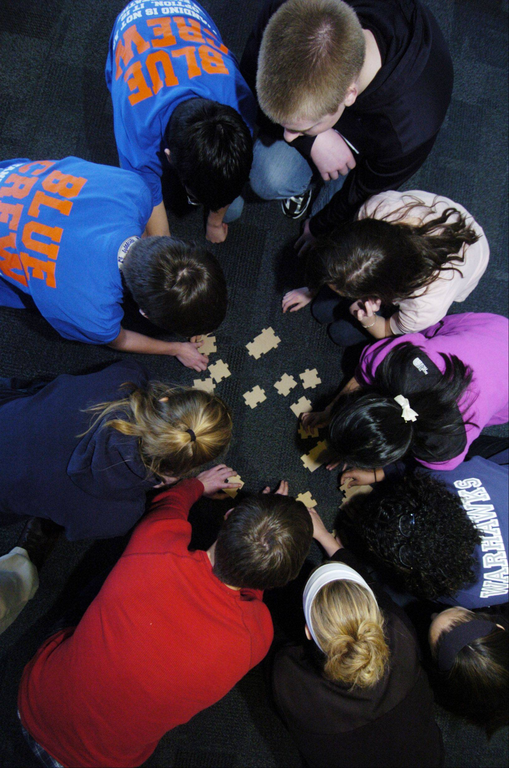 A group of students from High School District 211 work together to complete a puzzle with the pieces placed upside down during a new leadership event held at the Wojcik Conference Center in Palatine Thursday.