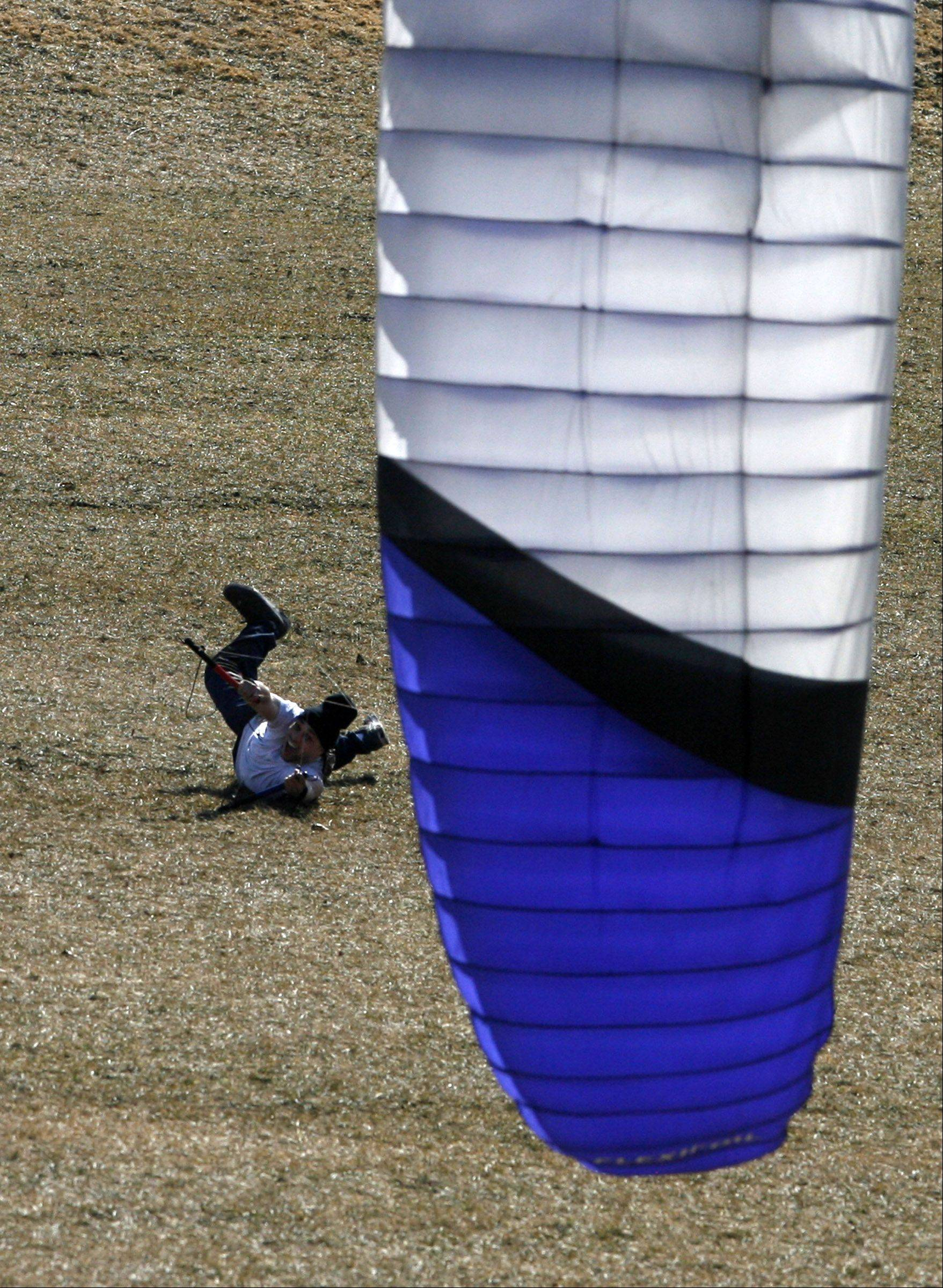 Frank Spencer of Des Plaines is dragged 30-feet by a 20-foot-wide kite as he attempts power kiting at Melas Park in Mount Prospect on Tuesday, March 6th. The $500 kite is owned by Spencer's friend Tom Zajkowski of Des Plaines who said the idea of the sport is to get off the ground.
