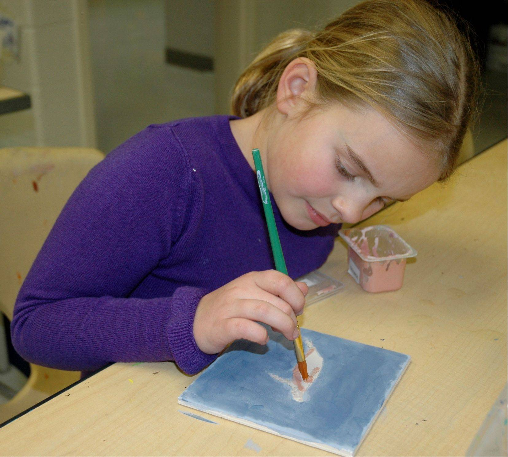 Third-grader Mary Zipfel paints tiles supplied by the Fremont Education Foundation. The tiles will eventually be applied to the wall behind the school's bathroom sinks.