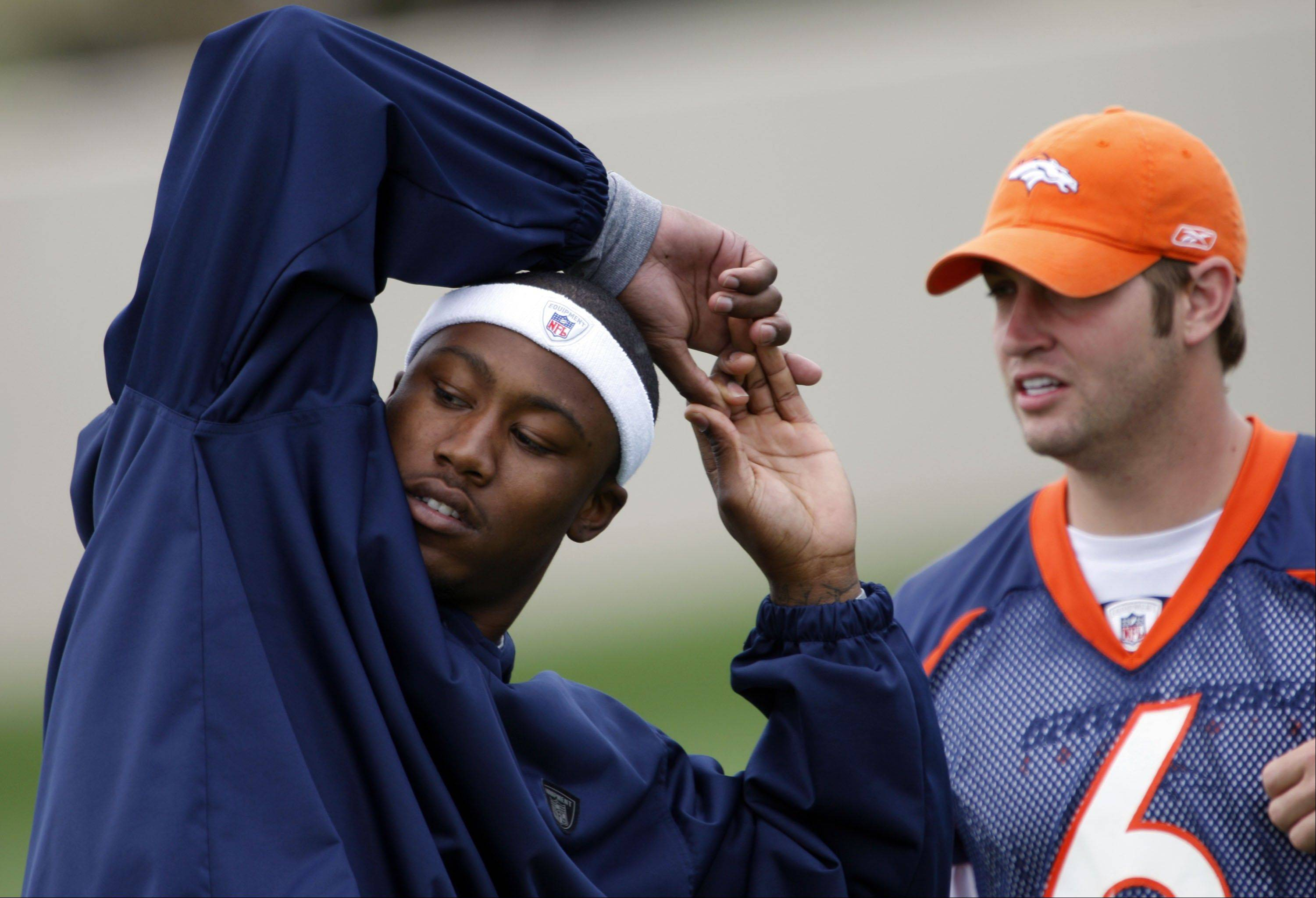Denver Broncos injured wide receiver Brandon Marshall, left, stretches as quarterback Jay Cutler looks on before taking part in the team's quarterback camp at the Broncos headquarters in southeast Denver on Wednesday, May 21, 2008.