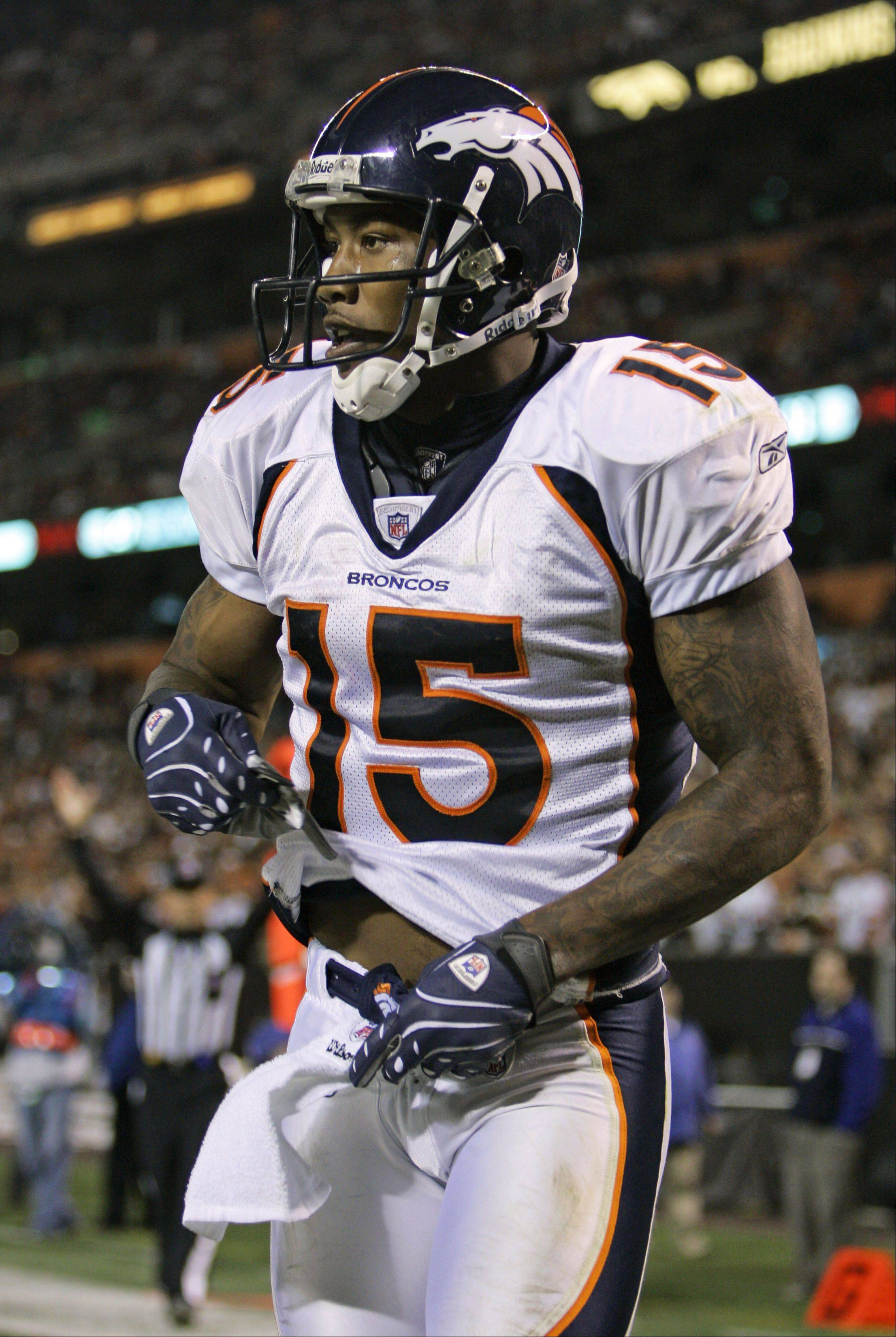 Denver Broncos wide receiver Brandon Marshall starts to pull a black-and-white glove designed to honor President-elect Barack Obama from his pants after an 11-yard touchdown catch in the fourth quarter of an NFL football game against the Cleveland Browns Thursday, Nov. 6, 2008, in Cleveland. Marshall was stopped by Brandon Stokley from possibly committing the personal foul.