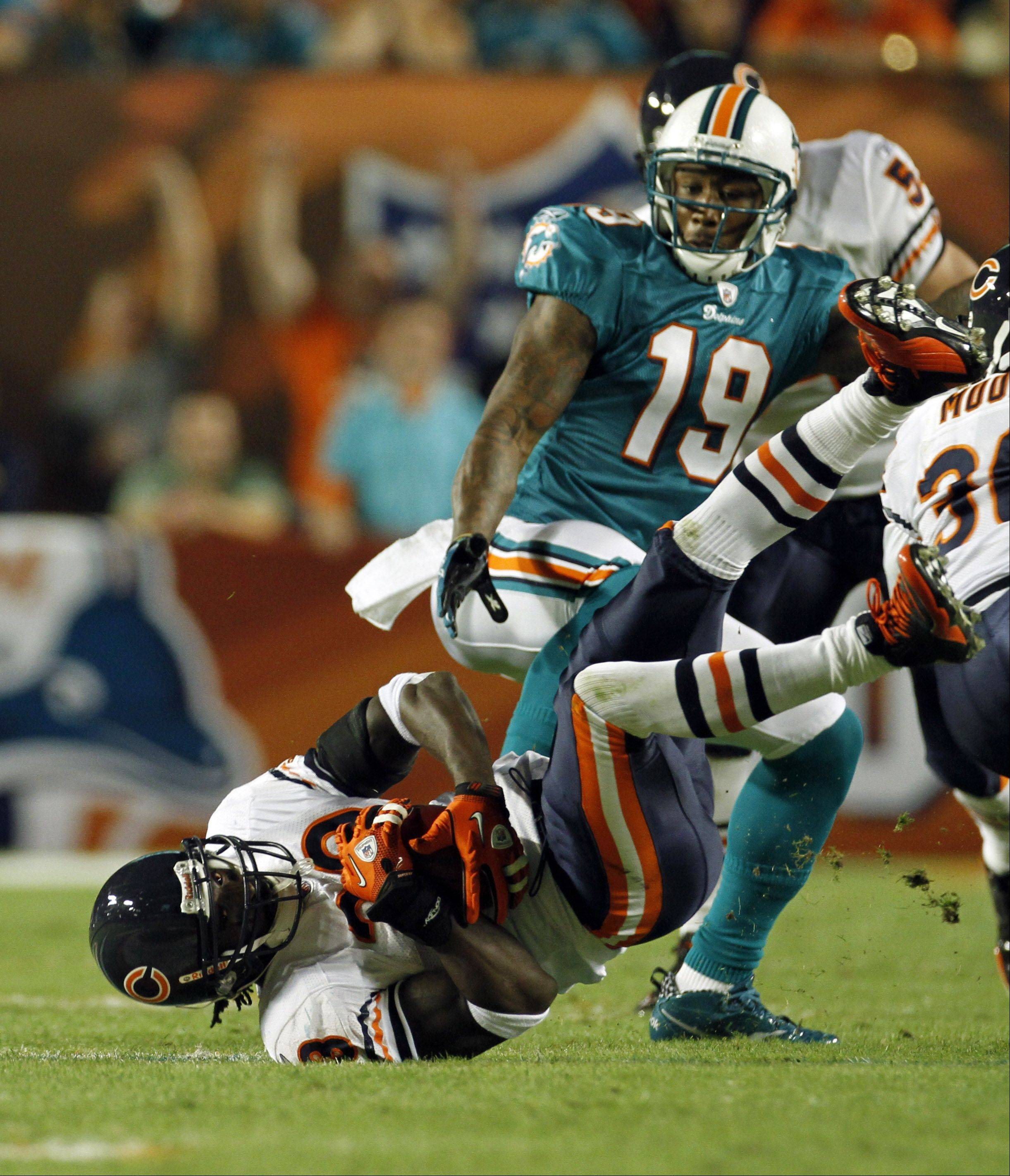 Chicago Bears cornerback Charles Tillman, lower left, intercepts a ball intended for Miami Dolphins wide receiver Brandon Marshall (19) during the first quarter of an NFL football game, Thursday, Nov. 18, 2010, in Miami.