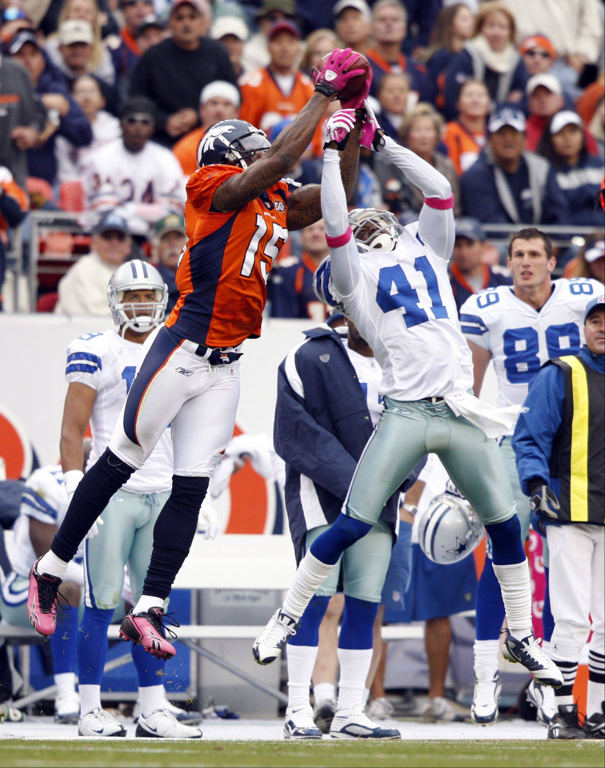 Denver Broncos wide receiver Brandon Marshall (15) catches a pass against Dallas Cowboys cornerback Terence Newman (41) for the game-winning touchdown during the fourth quarter of an NFL football game Sunday, Oct. 4, 2009, in Denver.