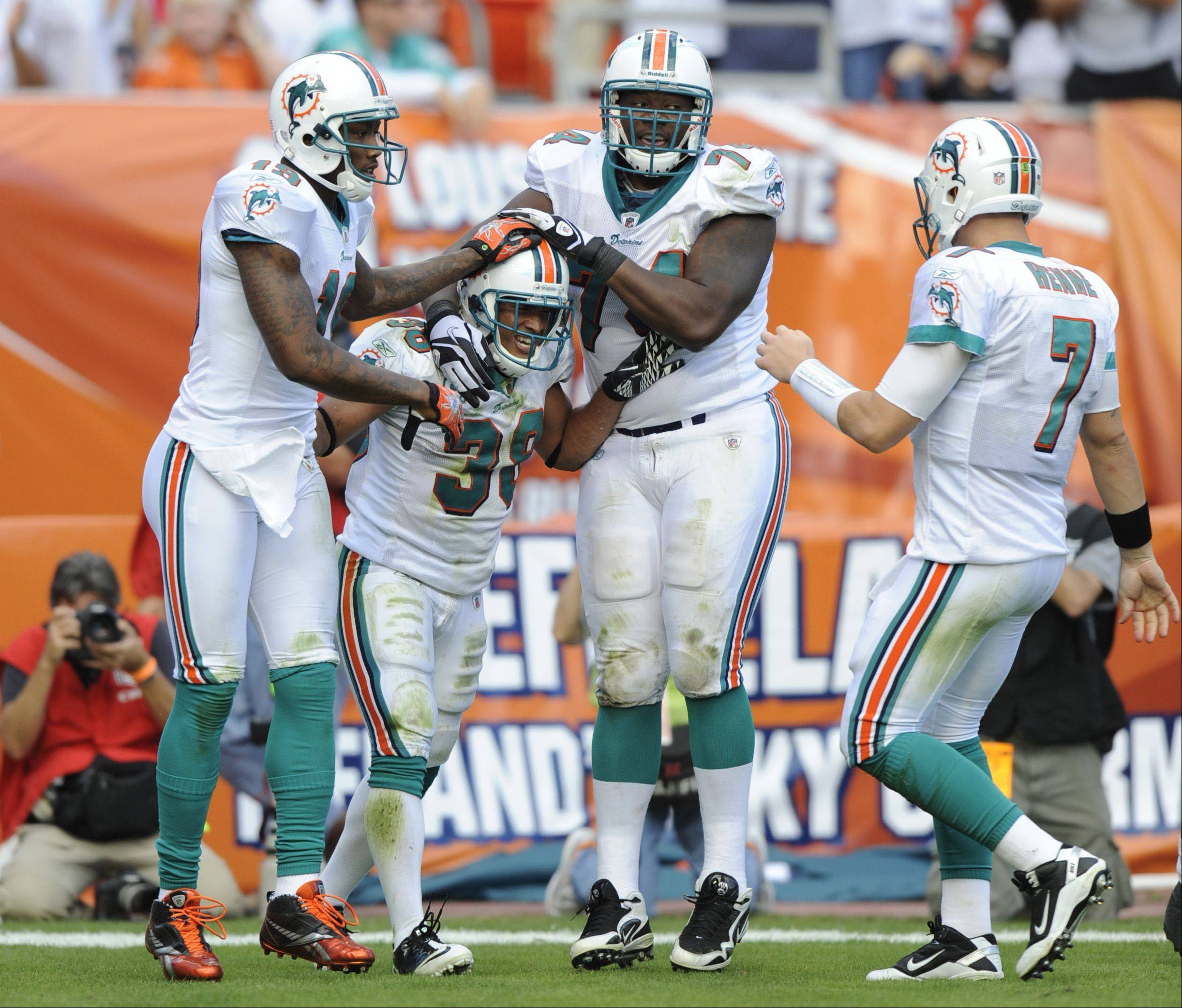 Miami Dolphins running back Patrick Cobbs (38) celebrates with wide receiver Brandon Marshall, left, guard John Jerry, second from right, and quarterback Chad Henne, right, after Cobbs scored a touchdown during the second half of an NFL football game against the Tennessee Titans on Sunday, Nov. 14, 2010 in Miami.