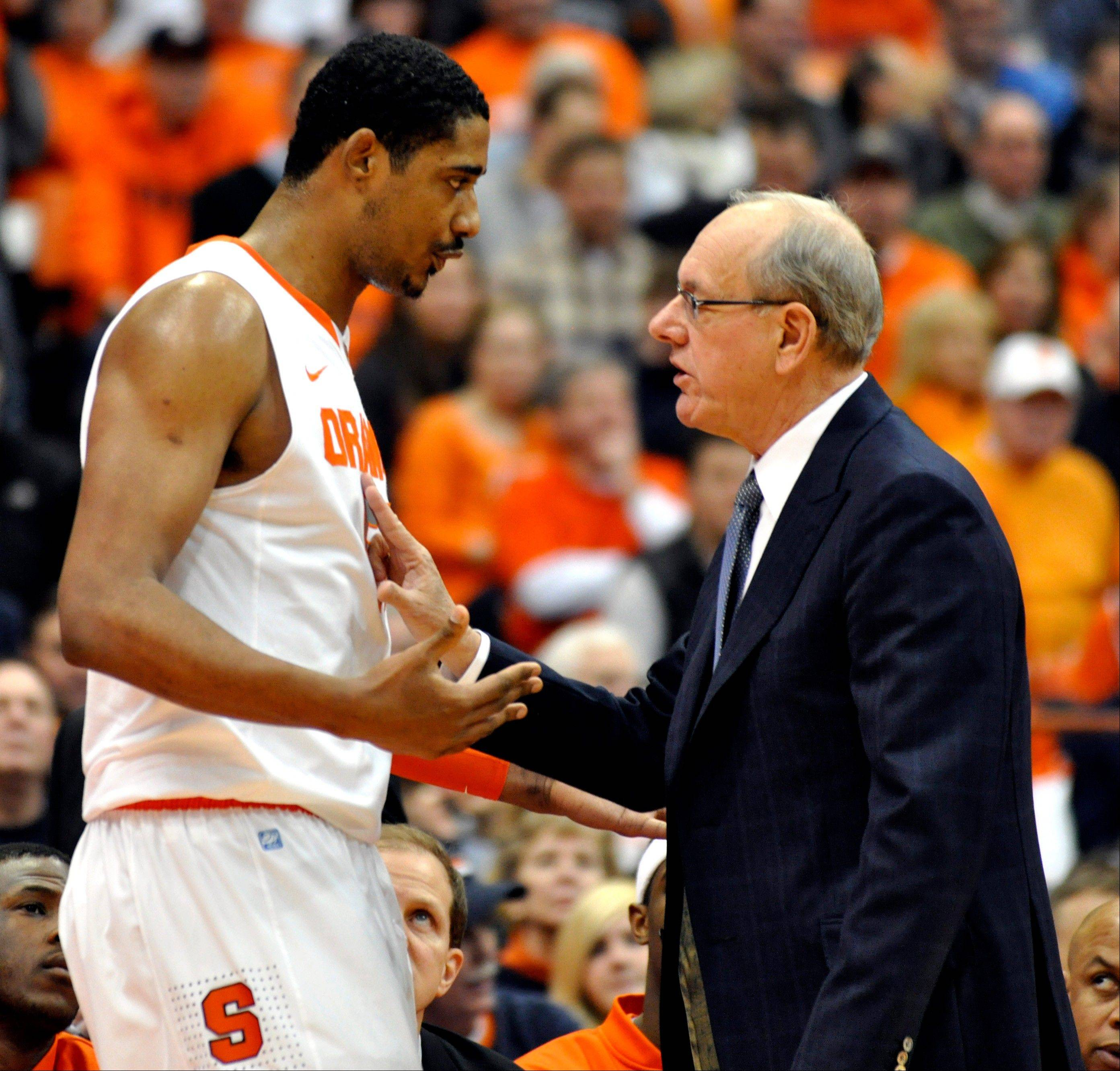 Syracuse head coach Jim Boeheim, right, talks with Fab Melo against Cincinnati. Melo did not travel with the team to Pittsburgh and the university says he won't take part in the NCAA tournament due to an eligibility issue. The school would not elaborate.