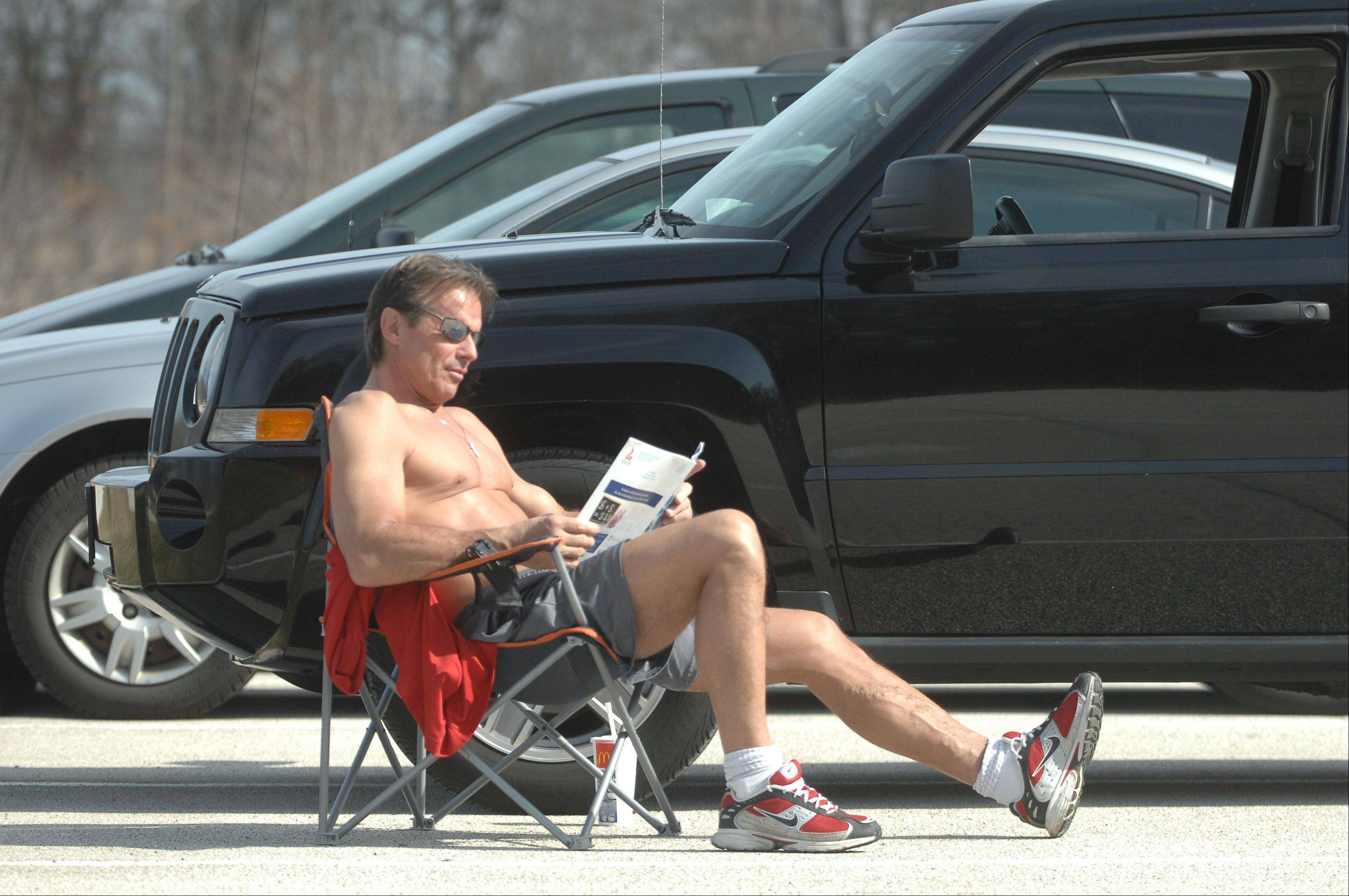 After a run in Independence Grove Forest Preserve, Libertyville resident Manny Piller took in some sun while reading and enjoying Wednesday's springlike weather.