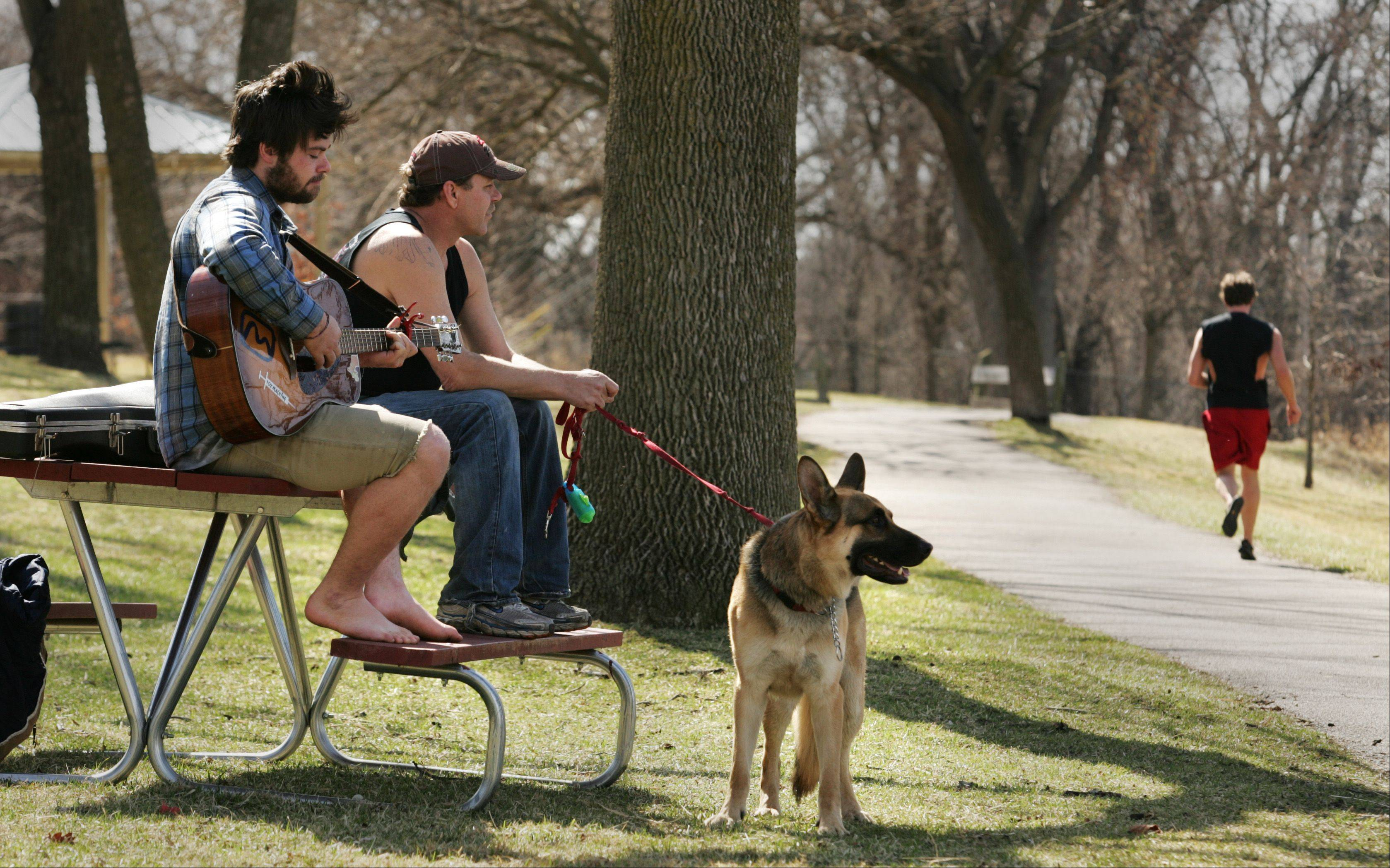 The warmest day so far in 2012 had Ben O'Brien of Geneva out along the Fox River with his guitar, his friend Don Ross, and Don's German shepherd, Hans, in Bennett Park. Runners, cyclists, walkers and picnickers were out in droves Tuesday as the sunshine made for a glorious day in the Fox Valley.