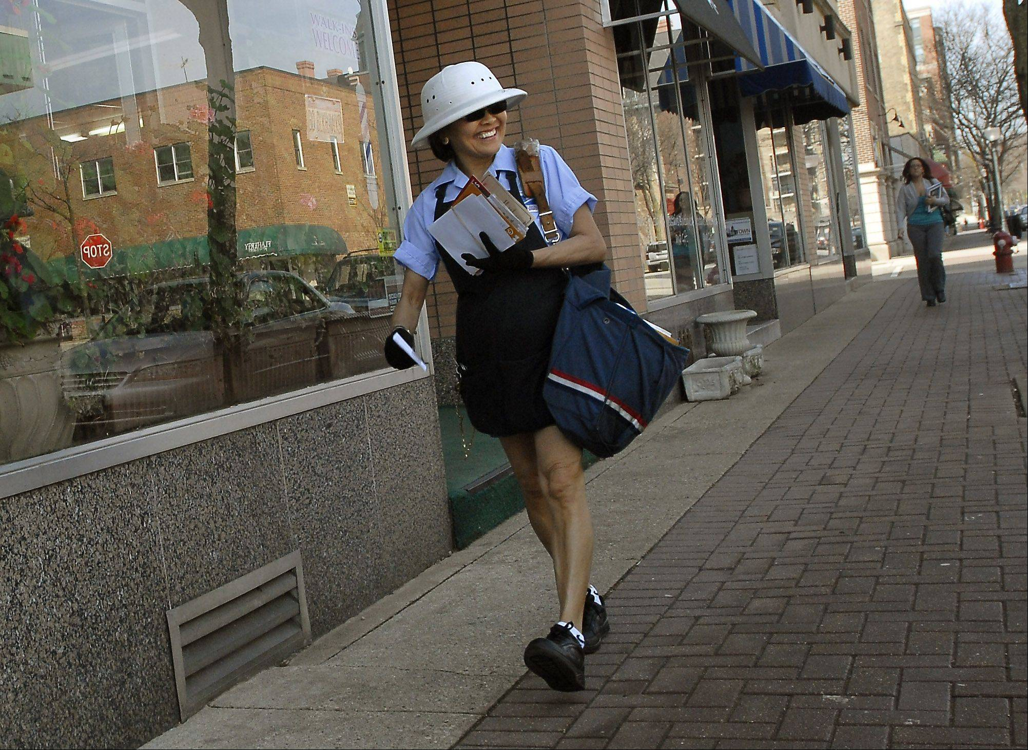 "Ching Velasquez, who has been delivering mail in downtown Arlington Heights for 24 years, smiles as she sees a familiar face on her route. With the temperature already at 70 degrees Wednesday morning, it was hard not to smile. ""I wait every day for weather like this. I love to wear coulottes, it feels so good."""