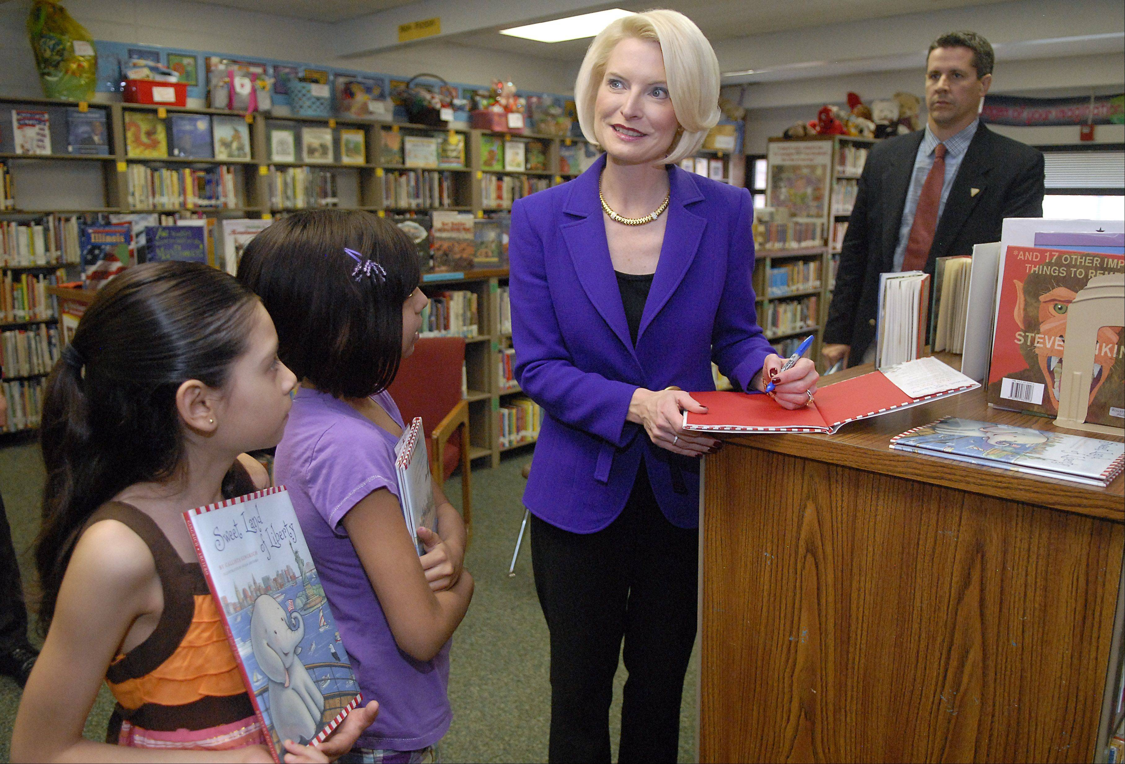 "Student council members and fourth graders Carolina Valdes, 8, left, and Natalie Loyola, 10, stand by while Callista Gingrich signs copies of her book ""Sweet Land of Liberty"" for Sunny Hill Elementary School in Carpentersville Thursday."