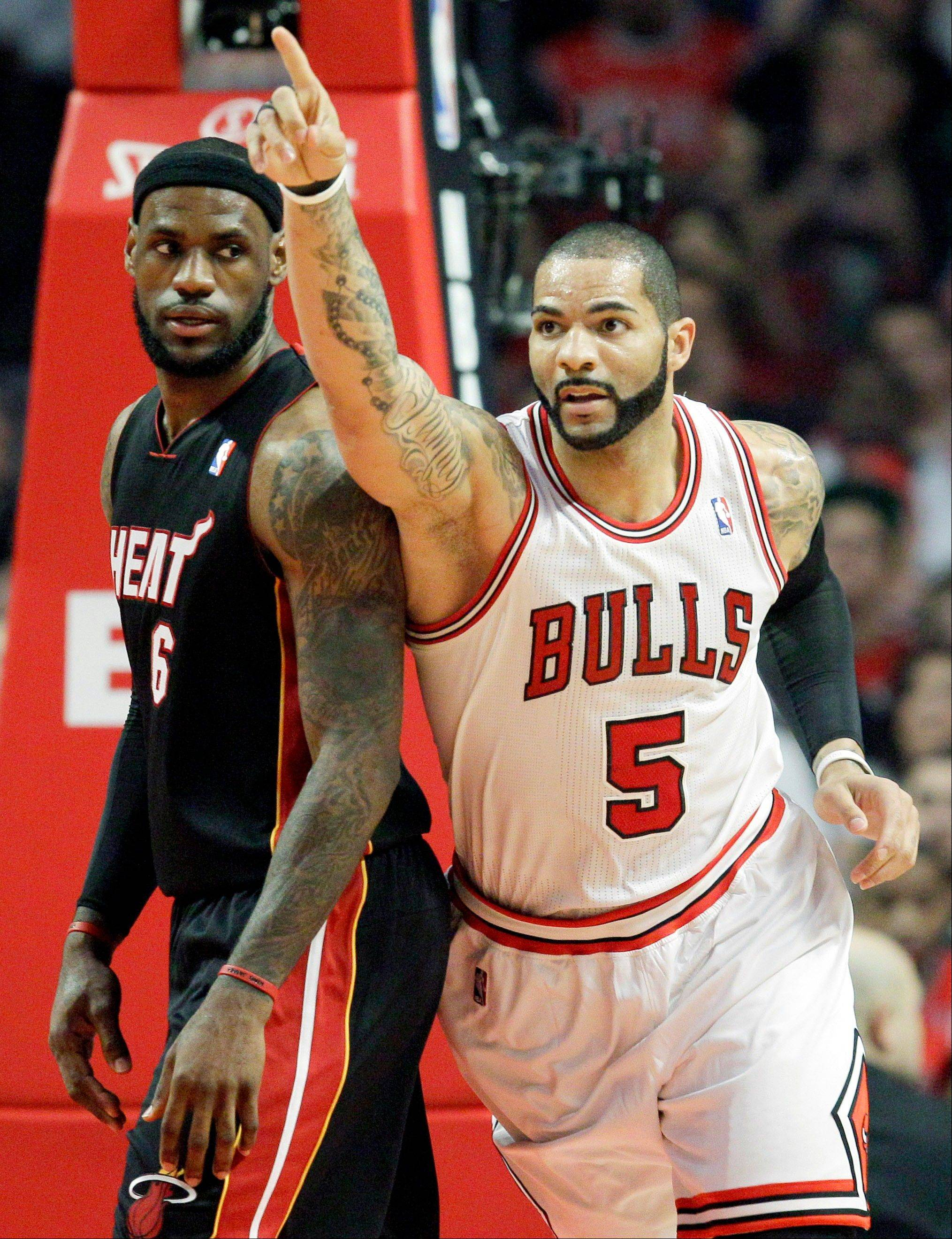 Caption credit:Associated Press Caption:Bulls forward Carlos Boozer celebrates Wednesday after scoring a basket in front of Miami Heat forward LeBron James during the first half.