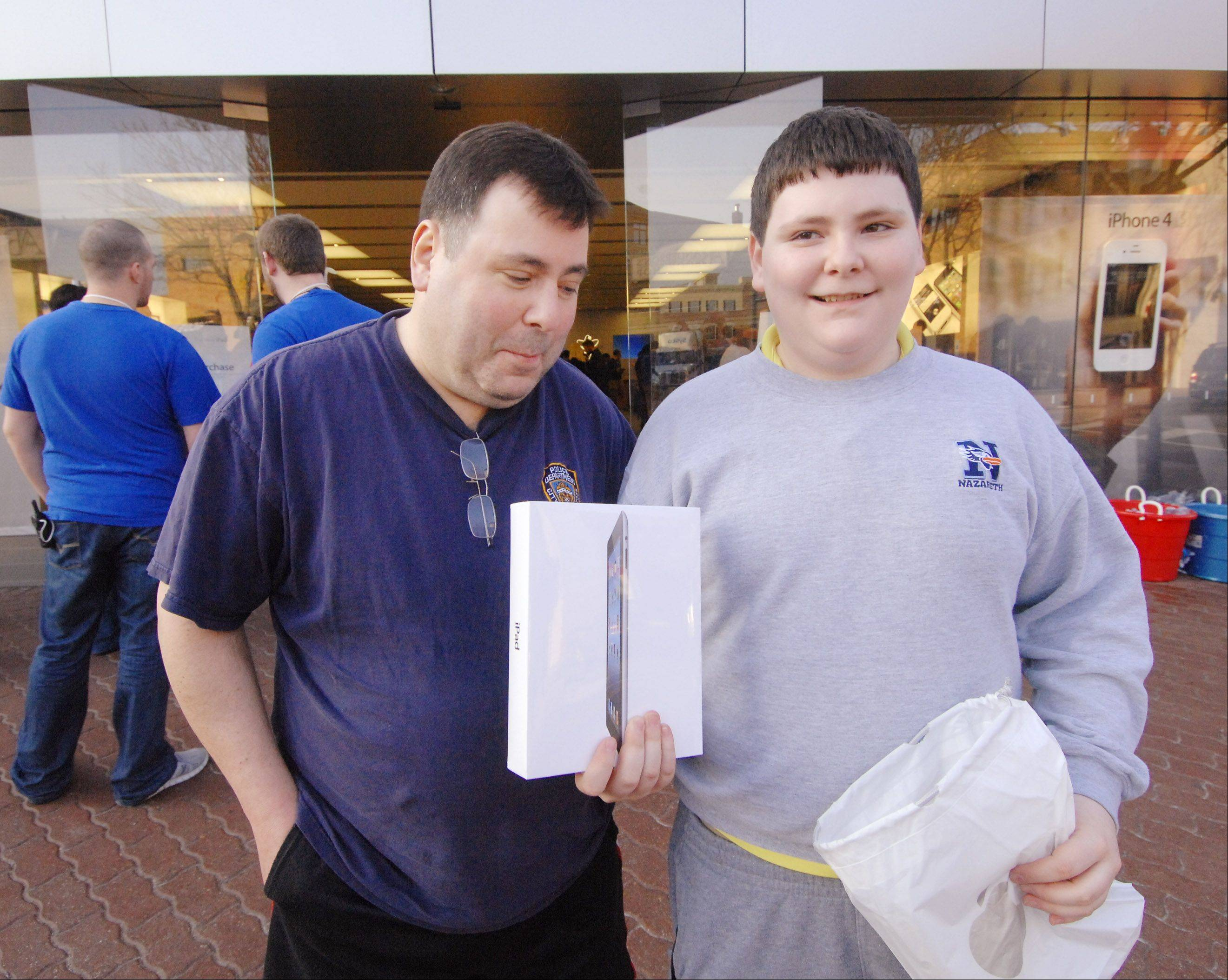 Matthew Henick, 14, emerges from the Apple store in Naperville with his new iPad after waiting overnight in line. His dad, Artie, sat in their car nearby all night.