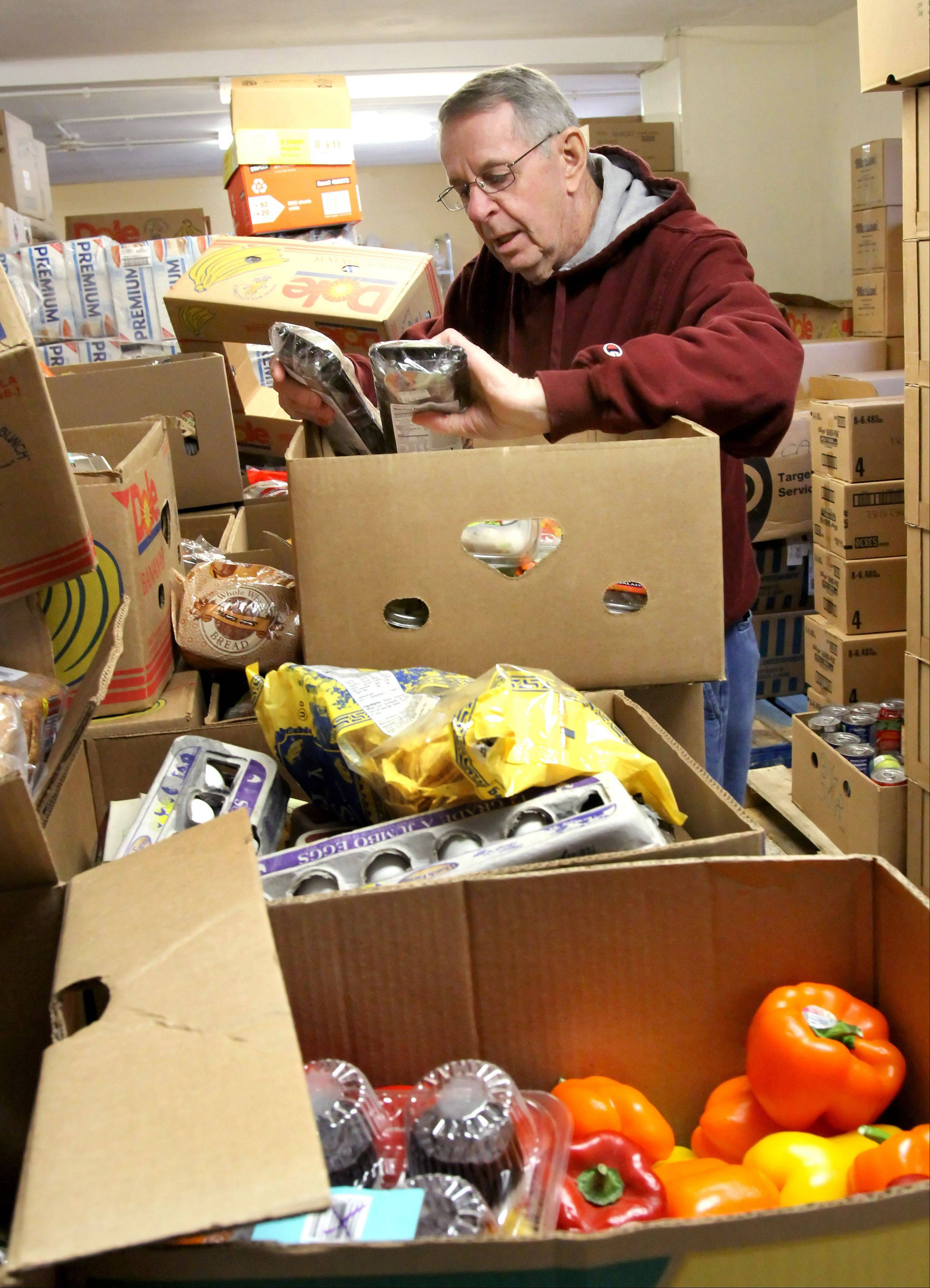 Don McGowan sorts through food that arrived at the People's Resource Center in Wheaton.